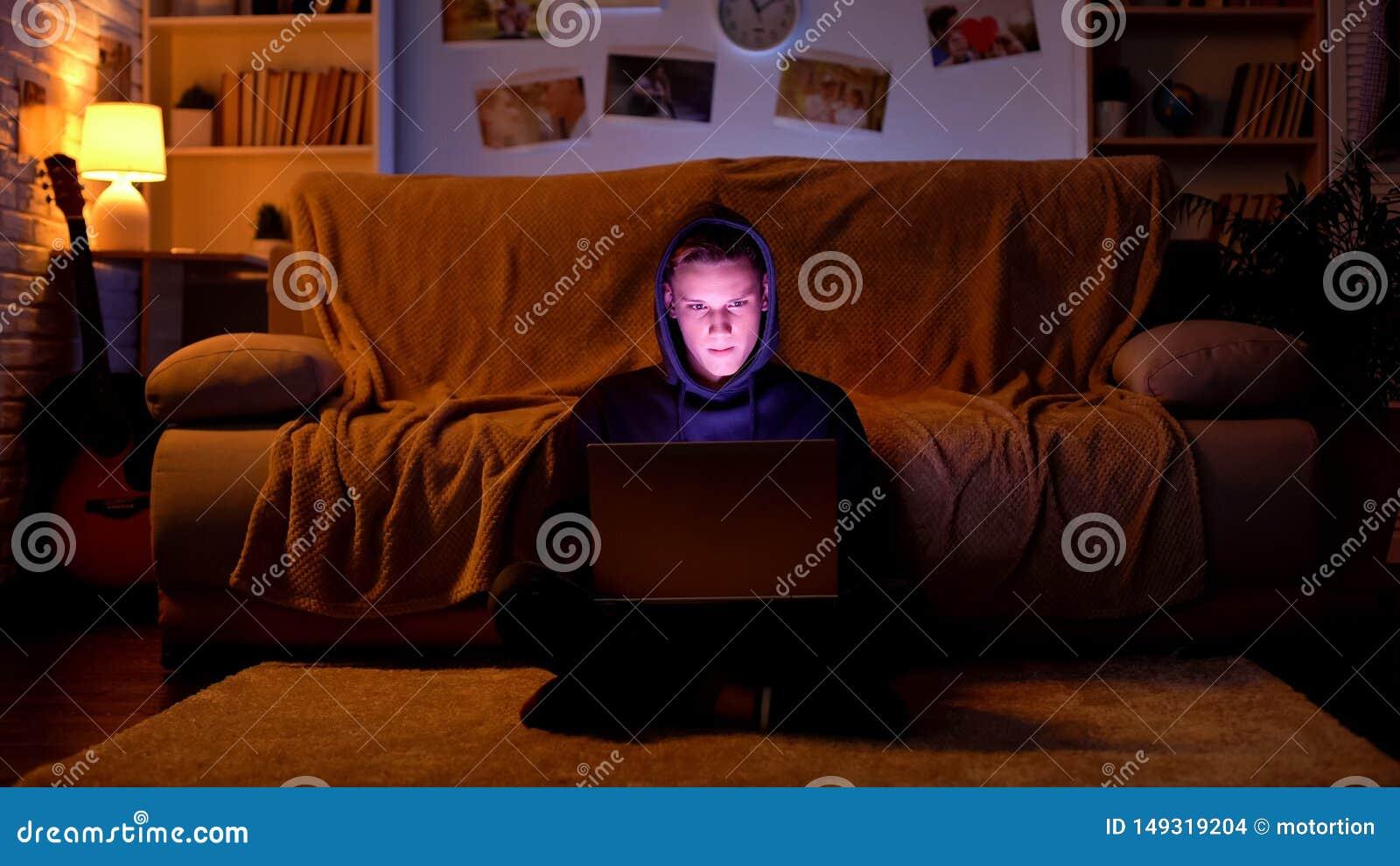 Nastolatek w kapiszonie bawi? si? gr? na laptopie lub ?ama stron? internetow?, cyber atak
