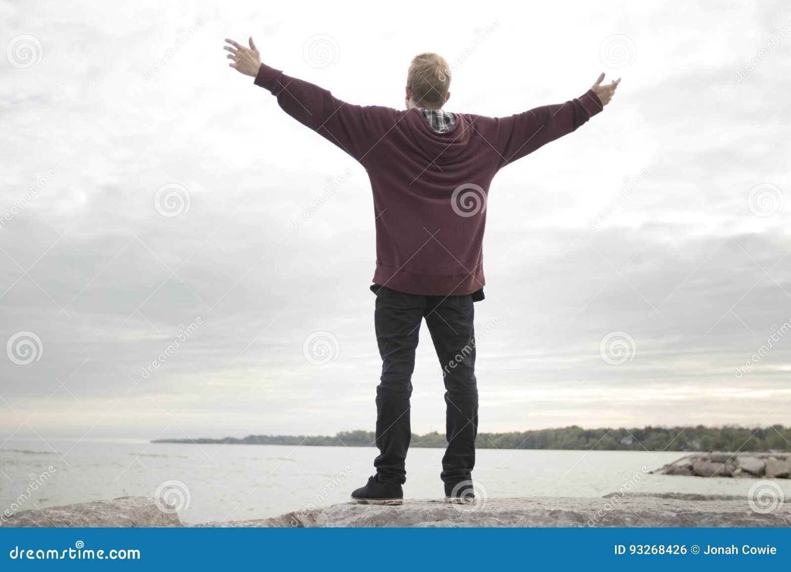 Nastolatek z rękami w powietrzu