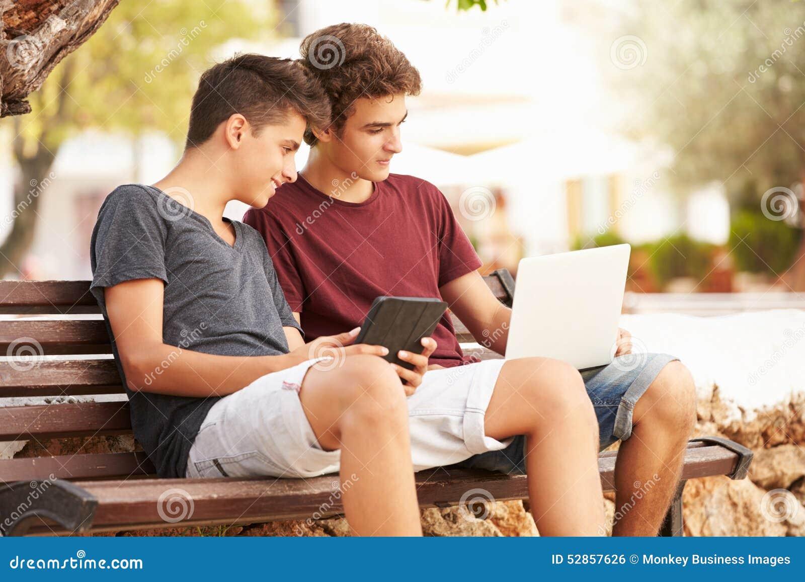 Nastoletni Chłopacy Na Parkowej ławce Używać laptop I Digital pastylkę