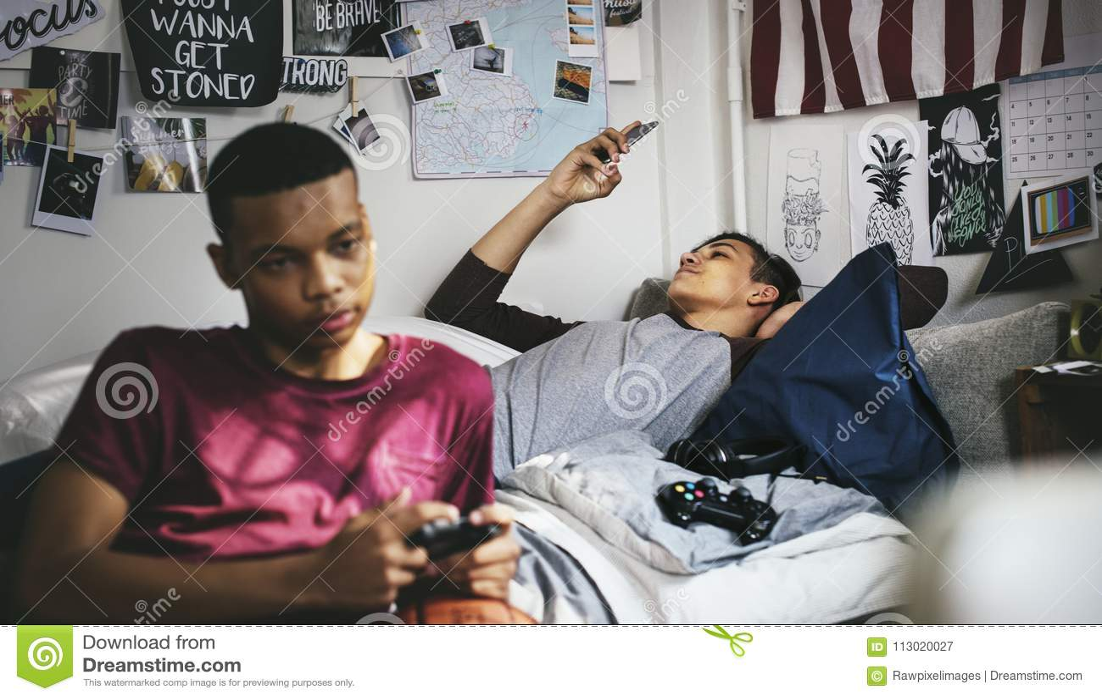 Nastoletni chłopacy wiszący w sypialni bawić się wideo grę i używa smartphone out