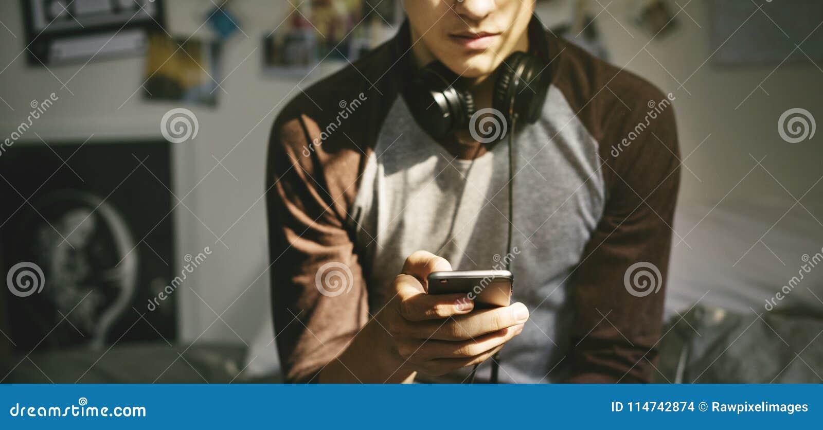 Nastoletni chłopak słucha muzyka przez jego smartphone w sypialni