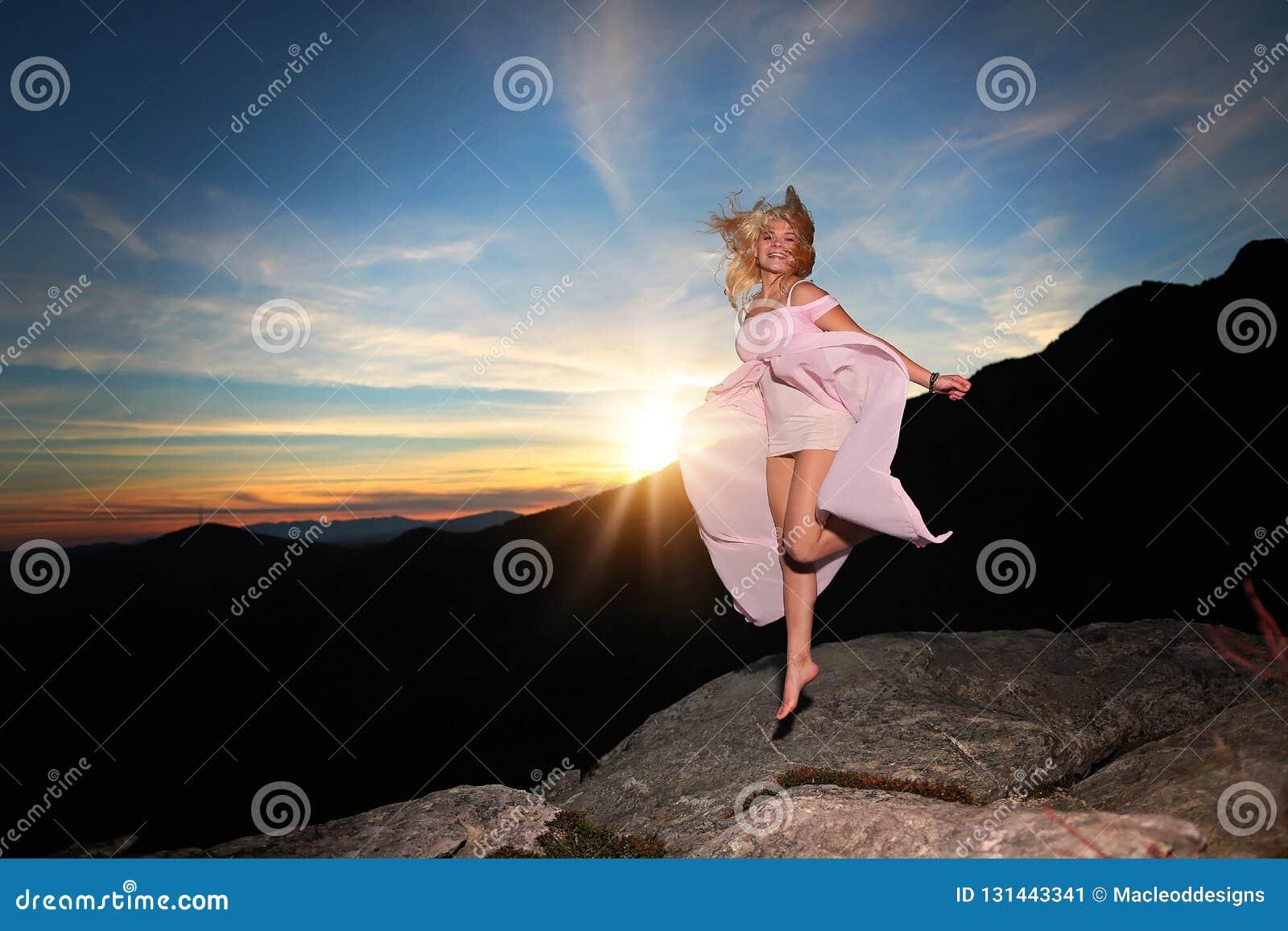 Nastoletni dziewczyna taniec na skale przegapia w górach