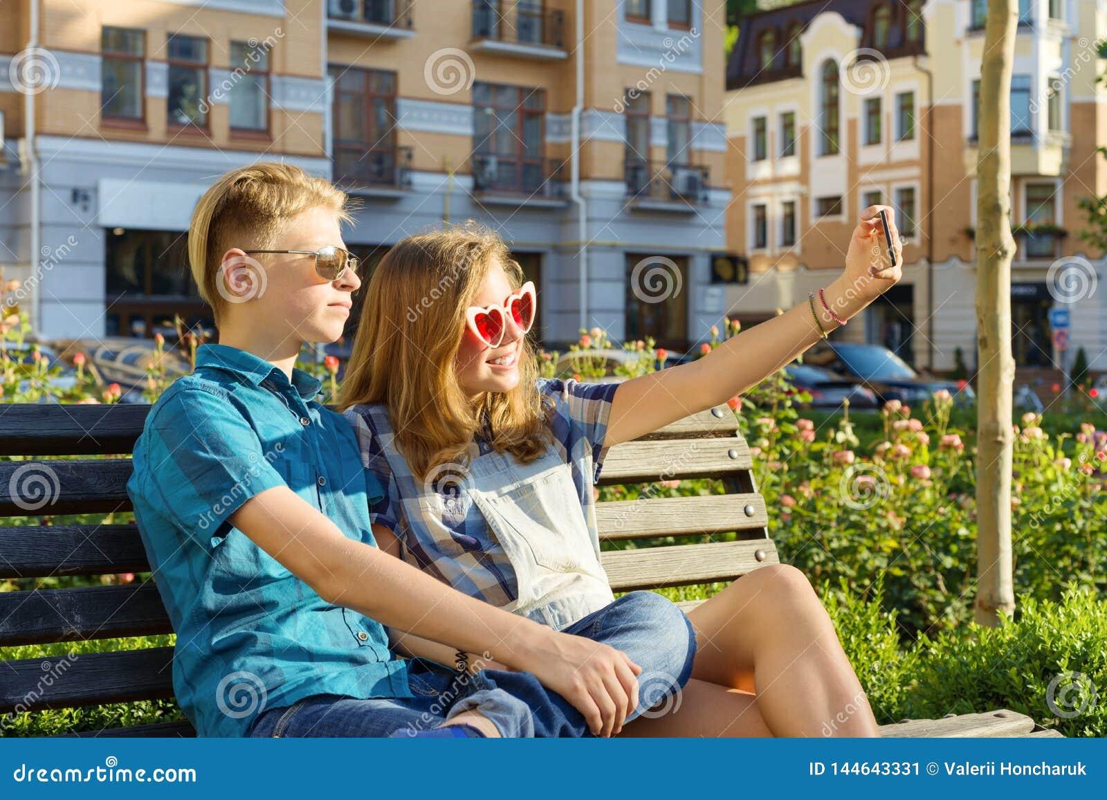 Nastoletni przyjaciele dziewczyna i chłopiec obsiadanie na ławce w mieście, opowiadający, patrzejący w telefonie, robi selfi