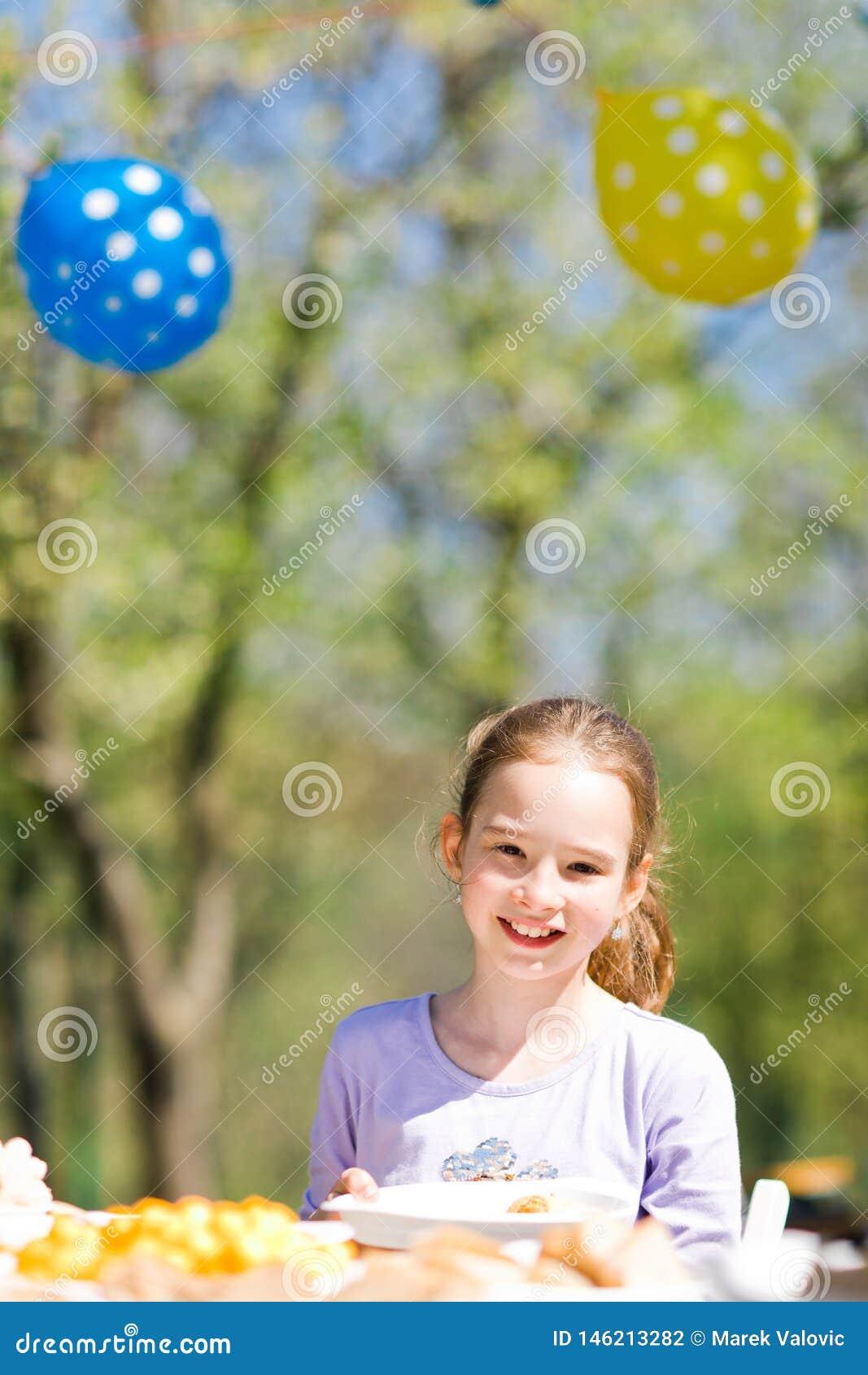 Nastoletni starzej?cy si? dziewczyny obsiadanie sto?em na urodzinowym ogrodowym przyj?ciu
