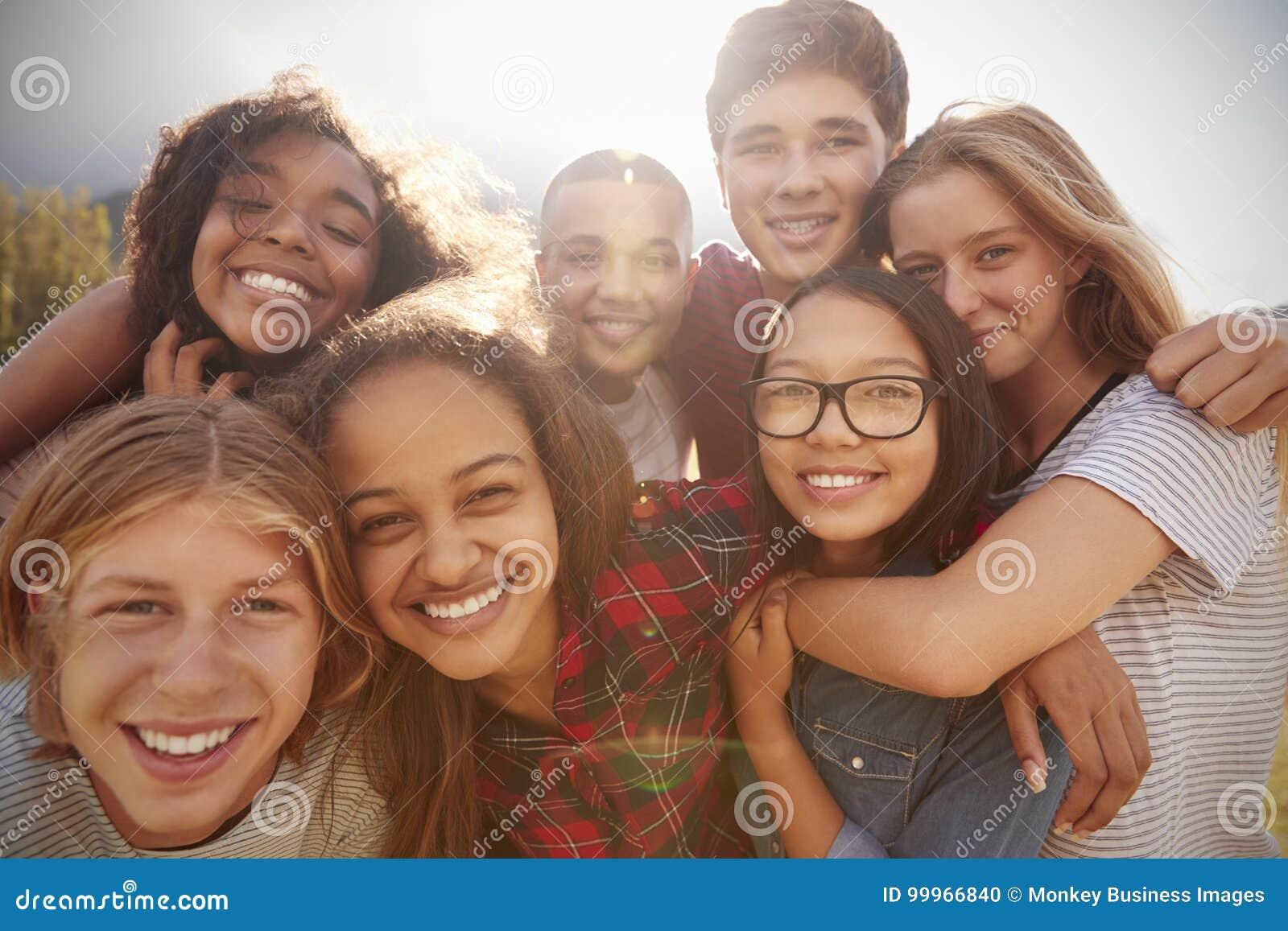 Nastoletni szkolni przyjaciele ono uśmiecha się kamera, zamykają up