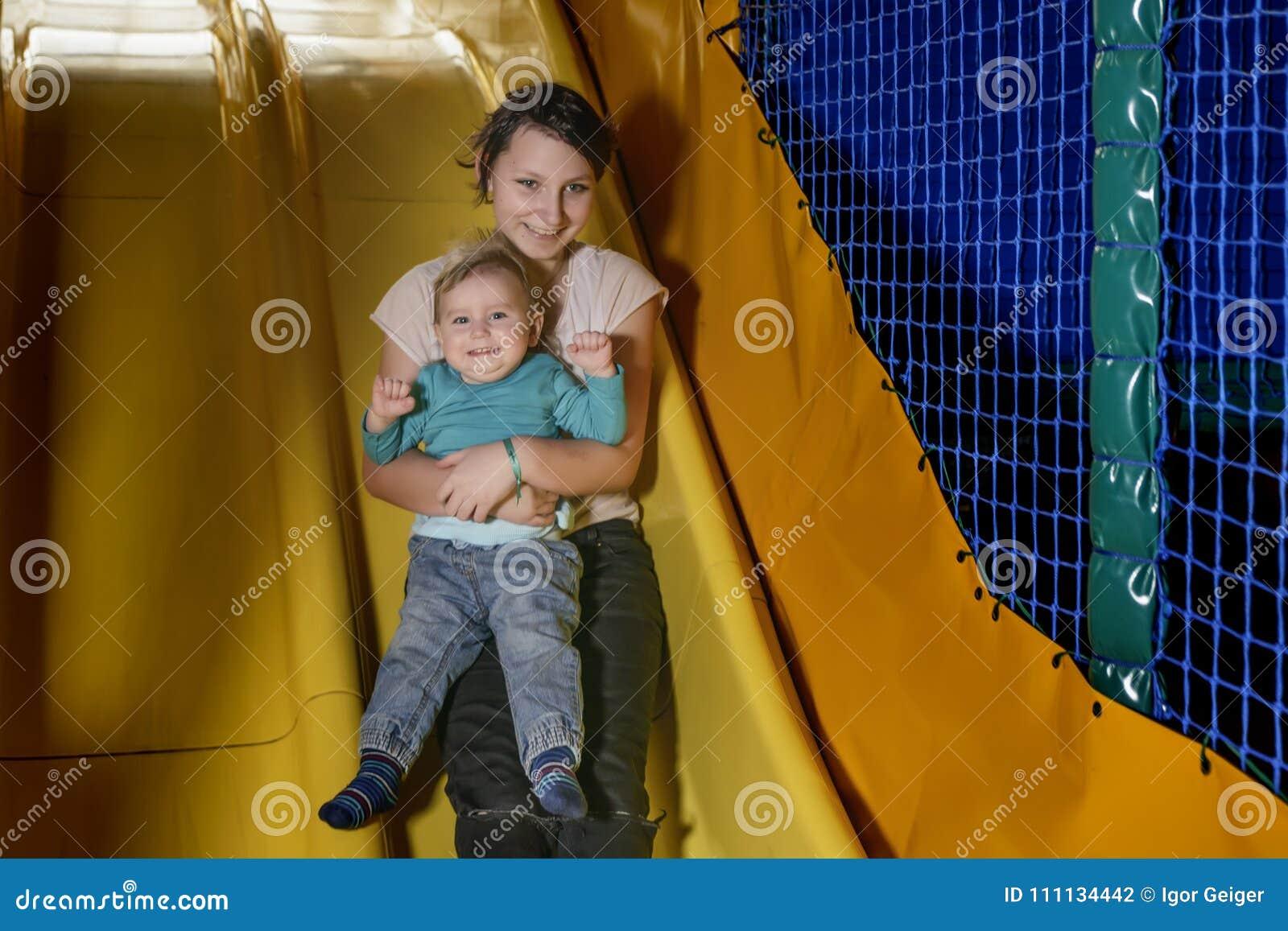 Nastoletnia dziewczyna i mały dziecko jesteśmy szczęśliwie tocznym puszkiem wzgórze