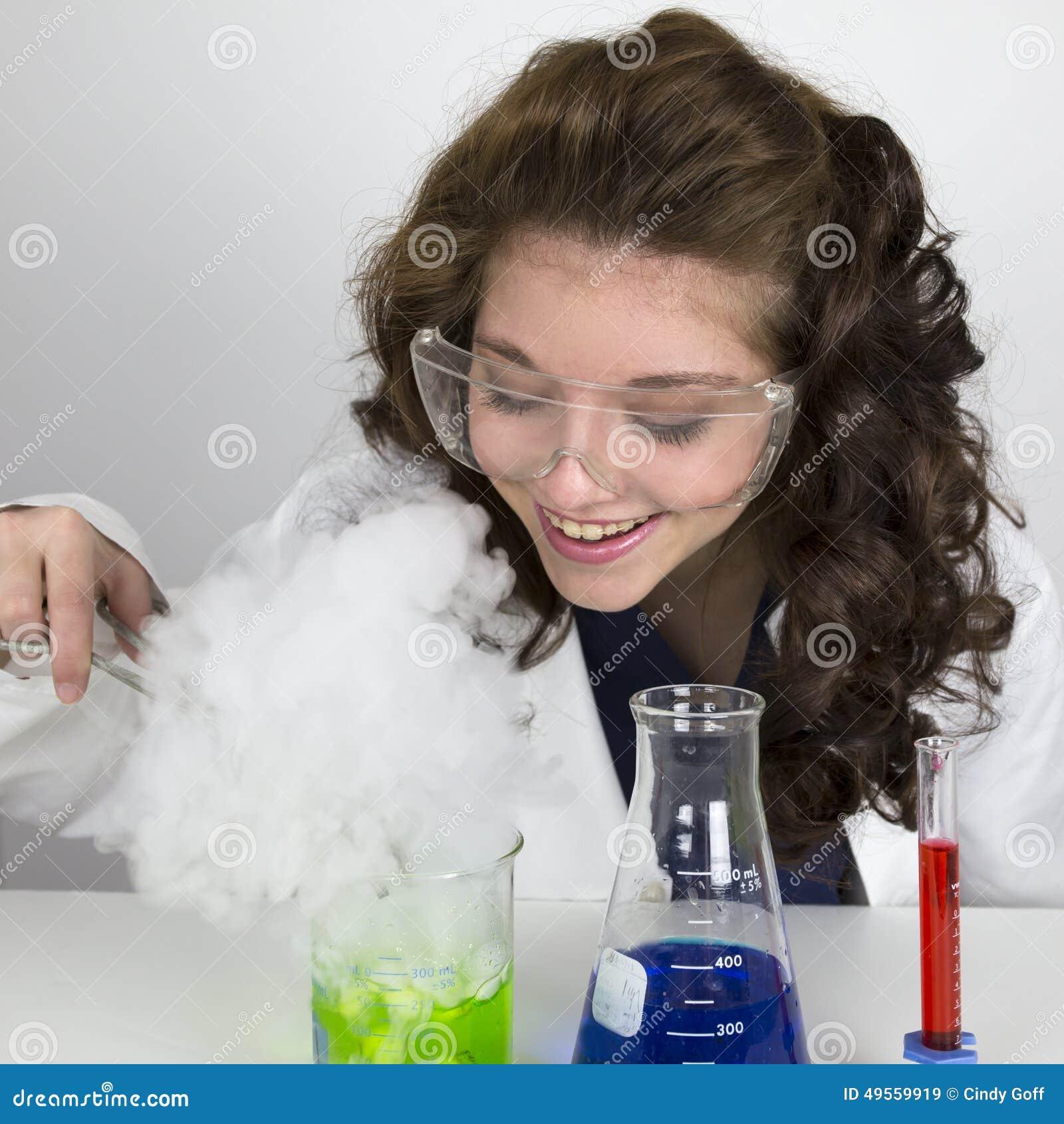Nastoletnia dziewczyna jest ubranym gogle robi nauka eksperymentowi