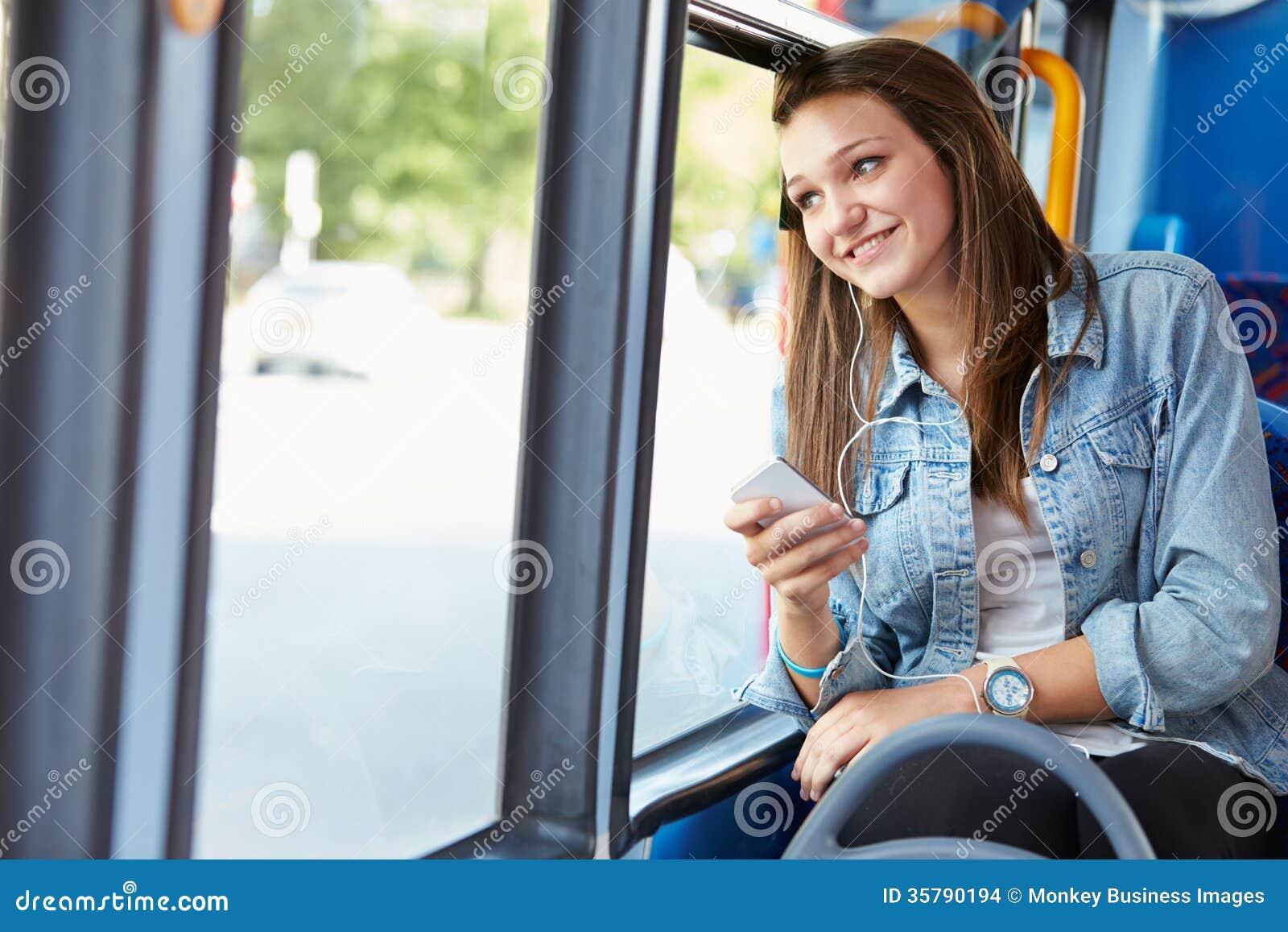 Nastoletnia Dziewczyna Jest ubranym słuchawki Słucha muzyka Na autobusie