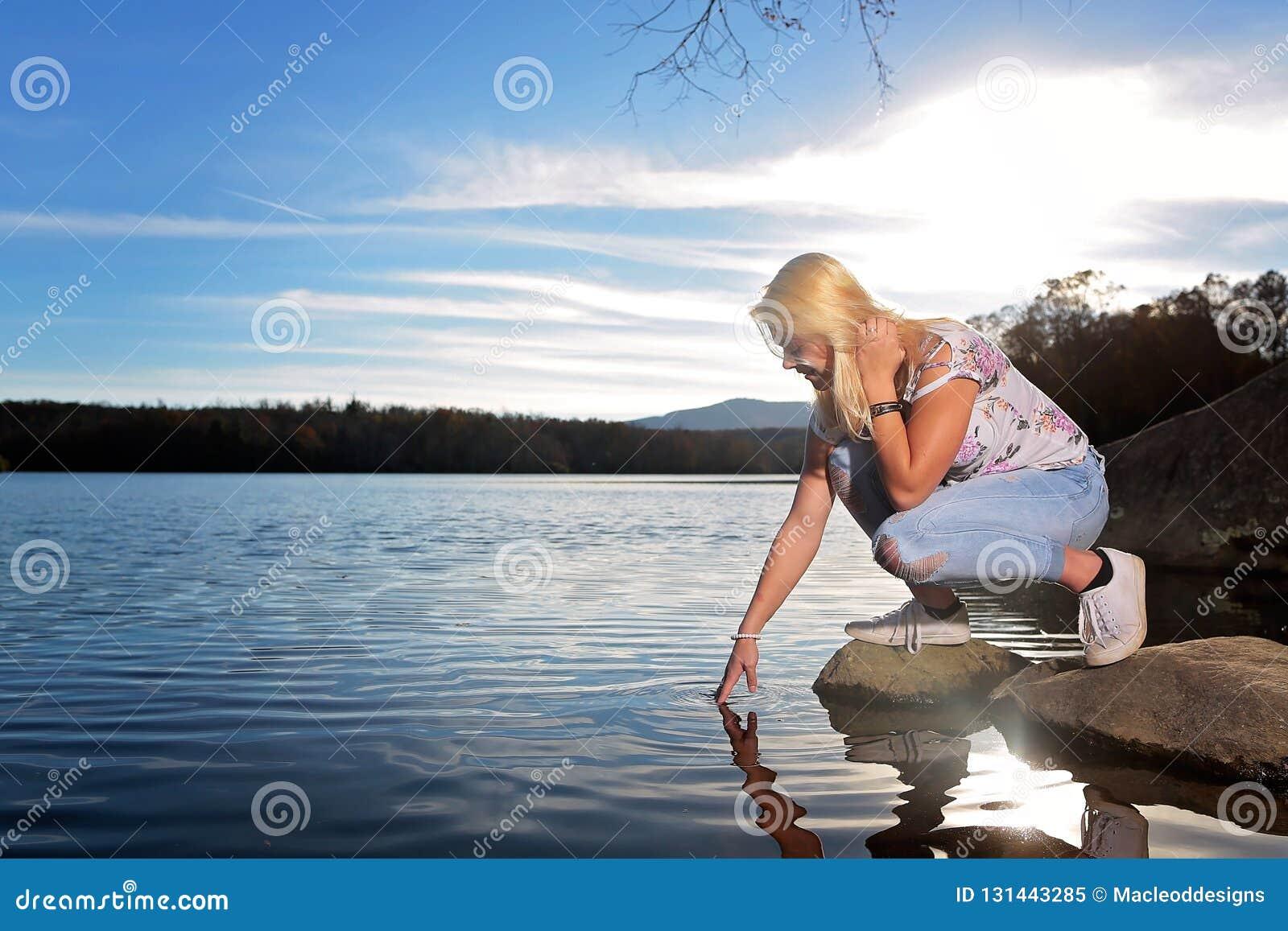 Nastoletnia dziewczyna na skale jeziorem