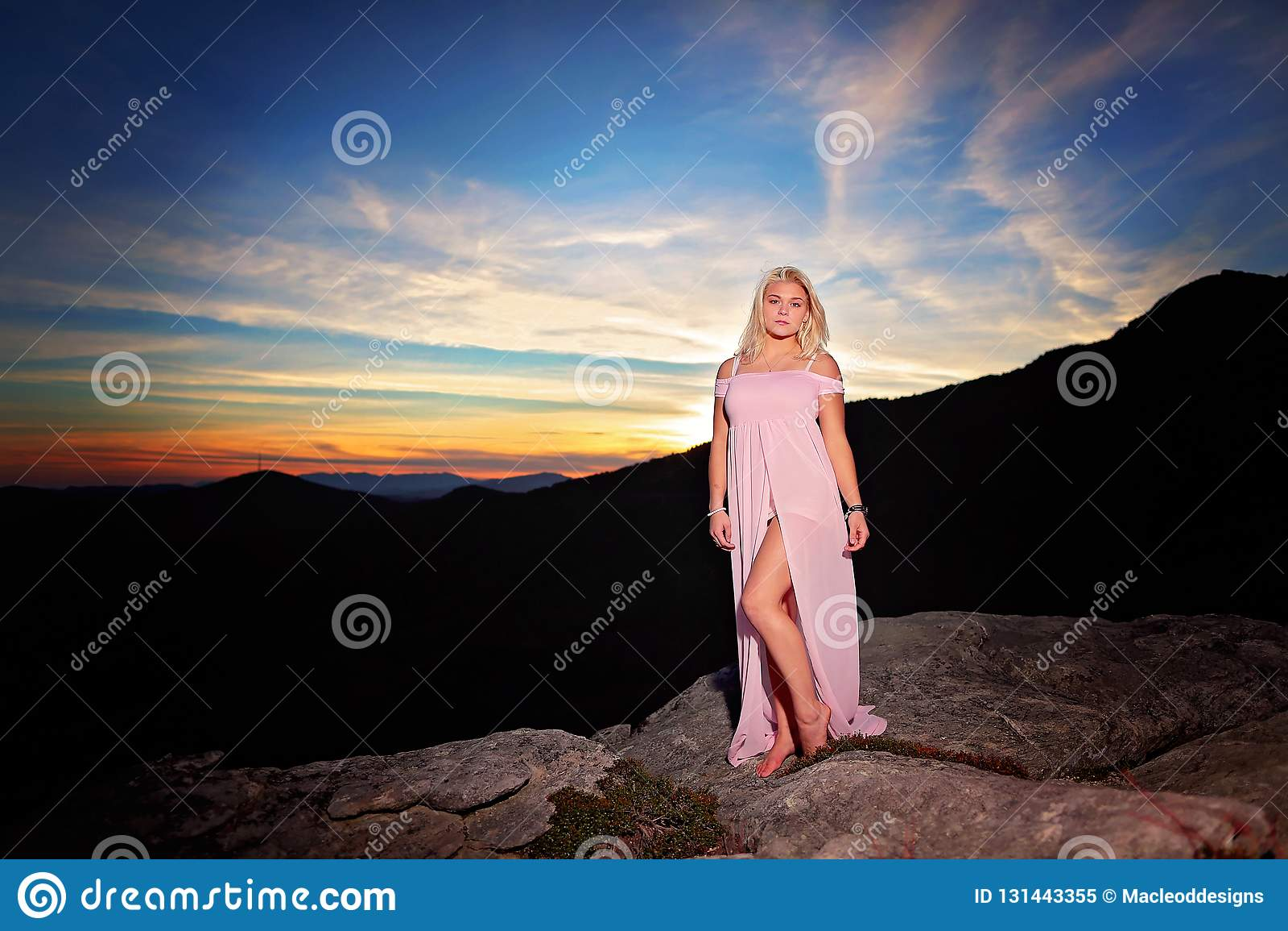 Nastoletnia dziewczyna na skale przegapia w górach