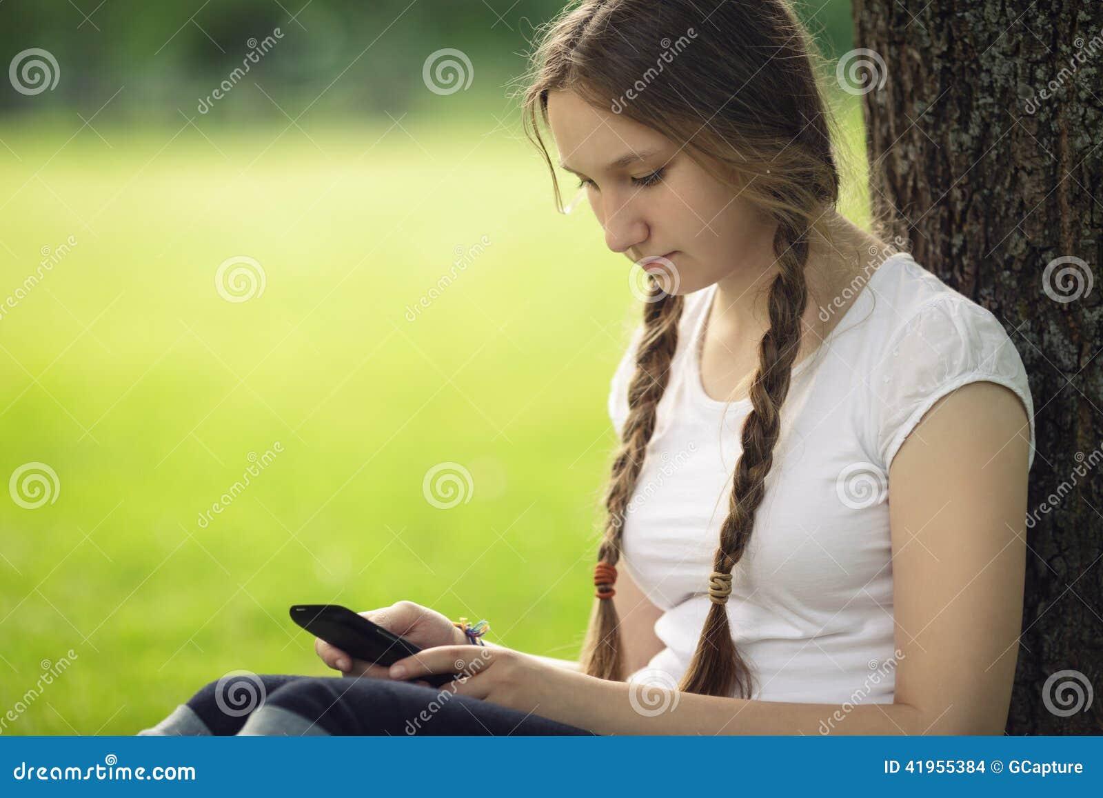 Nastoletnia dziewczyna siedzi blisko drzewa z telefonem kom