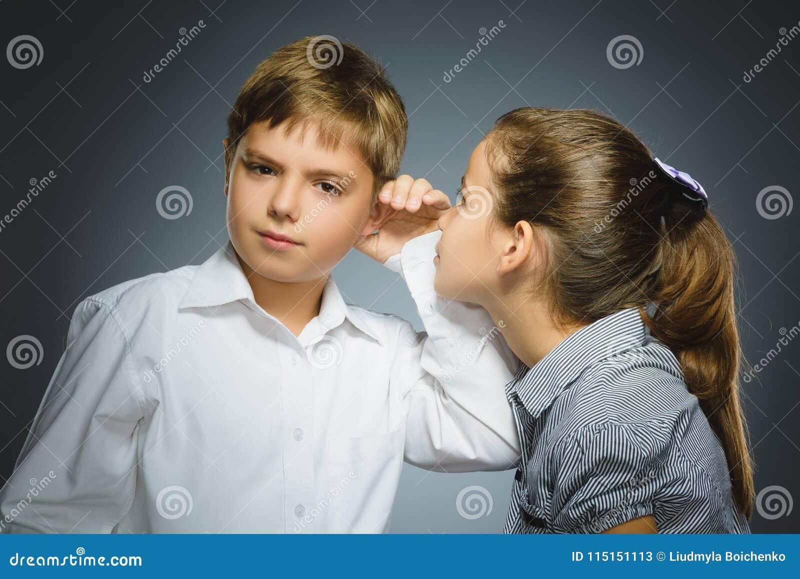 Nastoletnia dziewczyna szepcze w ucho chłopiec na szarym tle czarny komunikacji koncepcji odbiorców telefon
