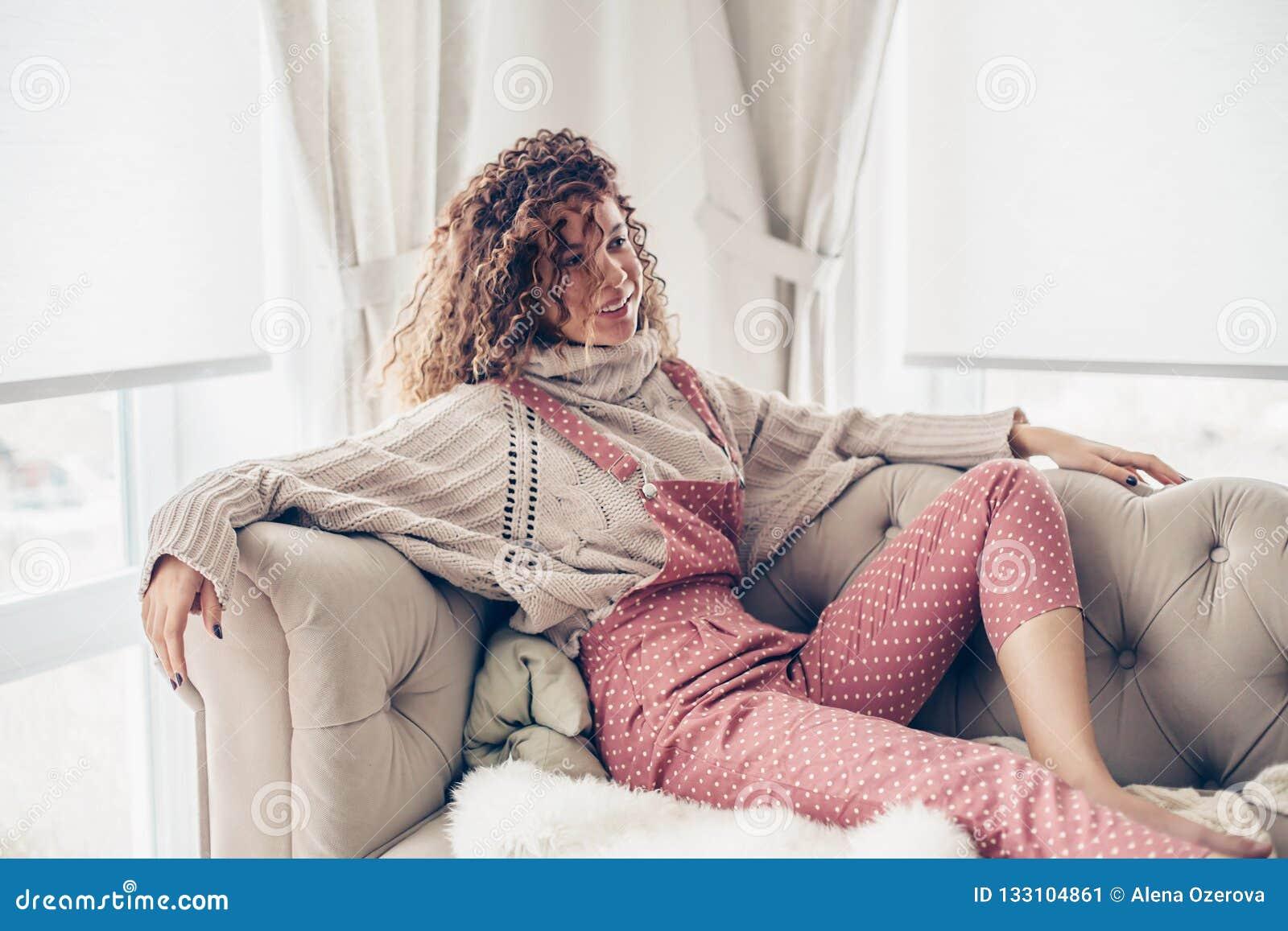Nastoletnia dziewczyna w pulowerze i kombinezonie na leżance