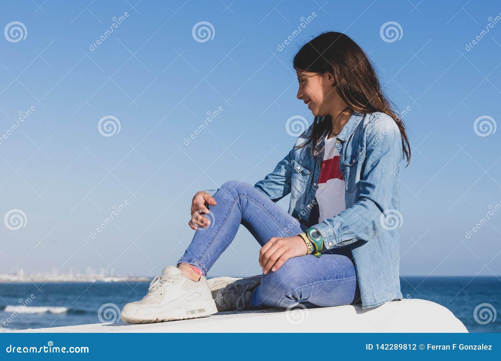 Nastoletnia dziewczyna z drelichu odzieżowym siedzącym obszyciem morze śródziemnomorskie w hiszpańskim miasteczku przybrzeżnym