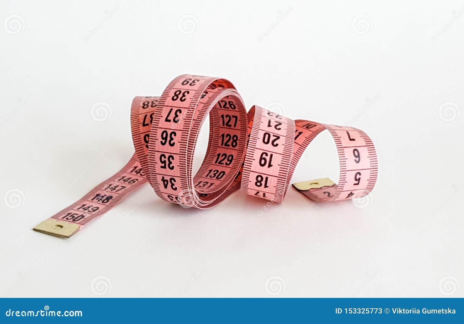 Nastro rosa di misura con i numeri neri su uno sfondo naturale bianco Chiuda su del nastro di misurazione Temi: dieta, fatta a ma