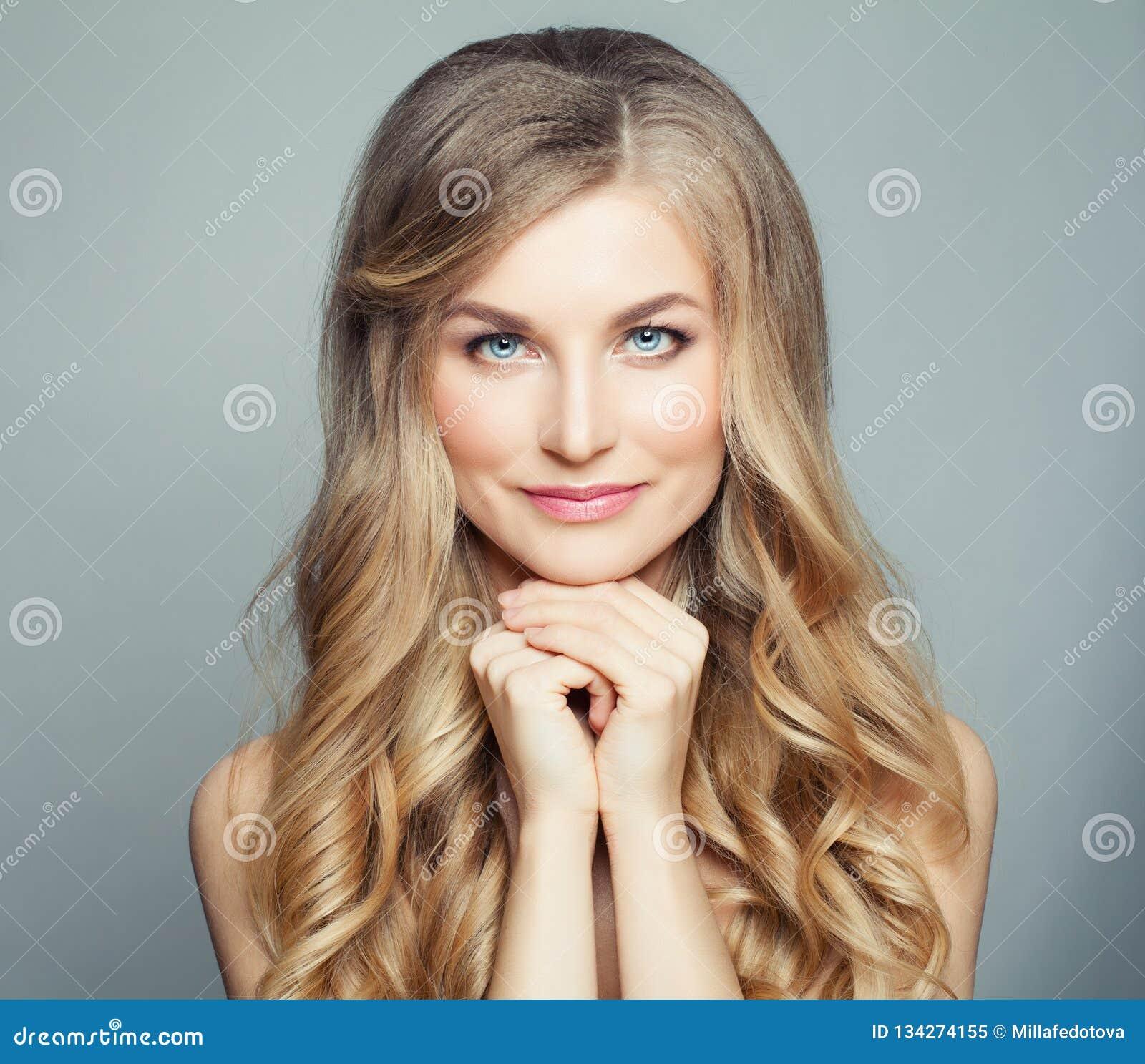 Natürliche Schönheit Blondine mit dem langen gesunden gelockten Haar und klarer Haut Gesichtsbehandlungs-, skincare- und Cosmetol