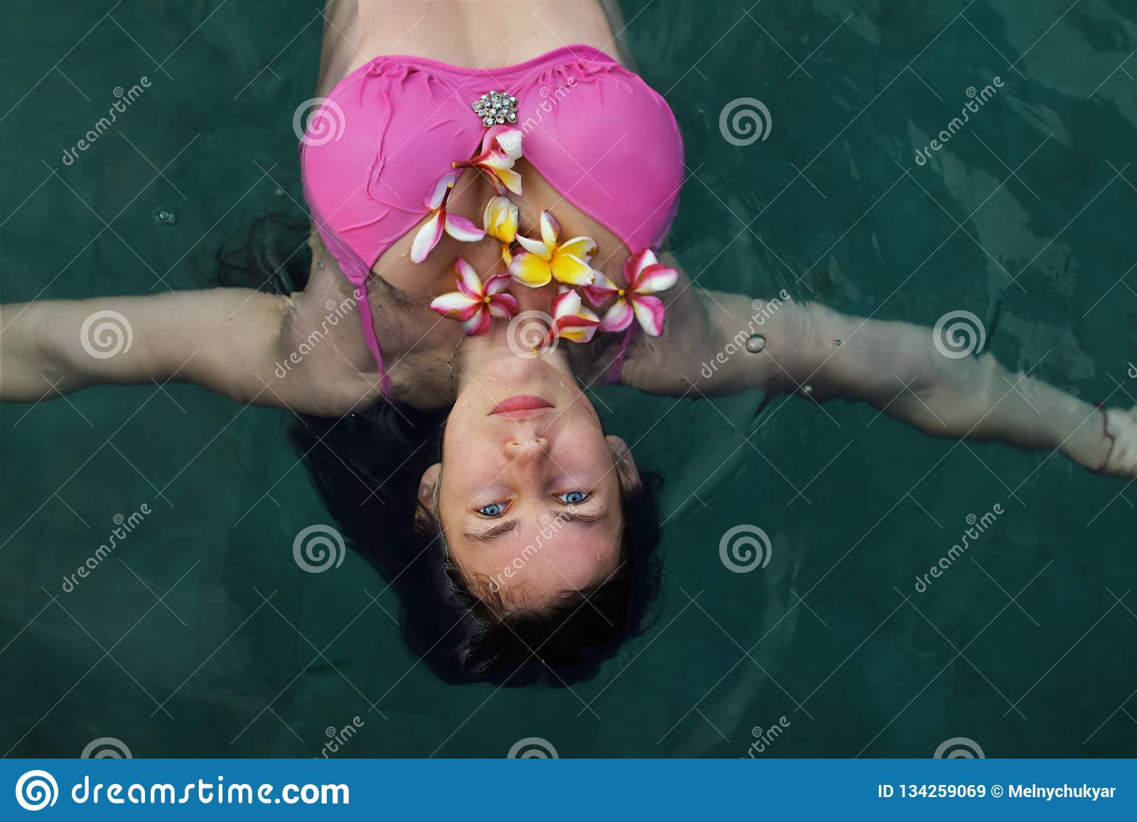 Natürliches Mädchen ohne Kosmetik, schöne junge Frauen mit Plumeriasblumen im blauen Swimmingpool