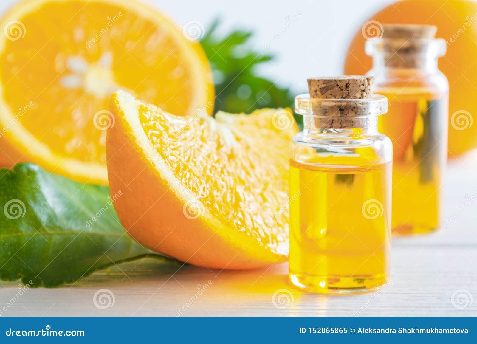 Natürliches Orangenöl in der Flasche und in der Schnittorangenfrucht auf weißem Holztisch