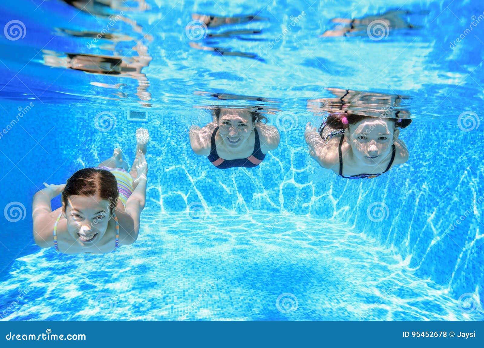 A natação da família na associação sob a água, a mãe ativa feliz e as crianças têm o divertimento, a aptidão e o esporte com cria