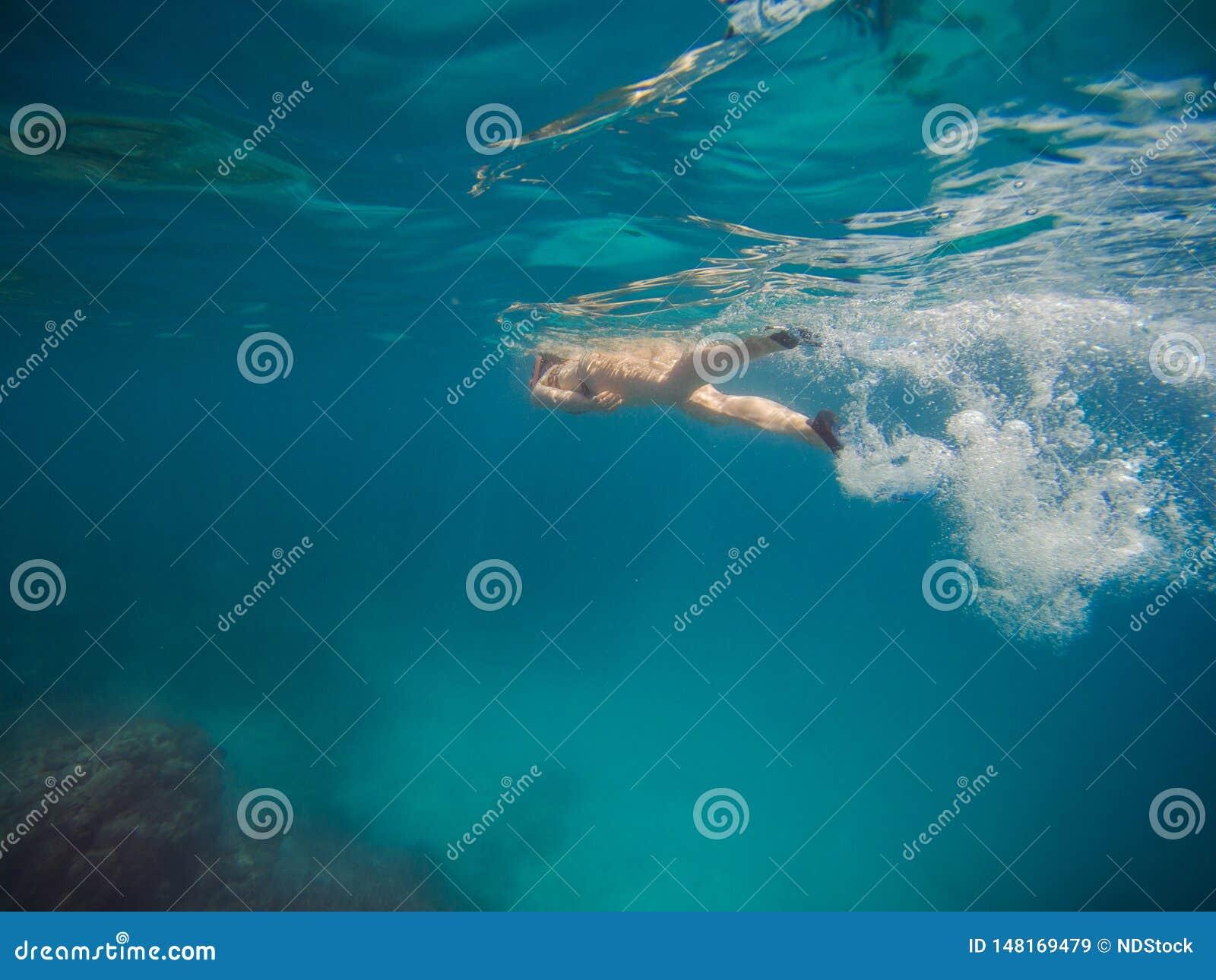 Natação da jovem mulher e mergulhar com máscara e aletas na água azul clara