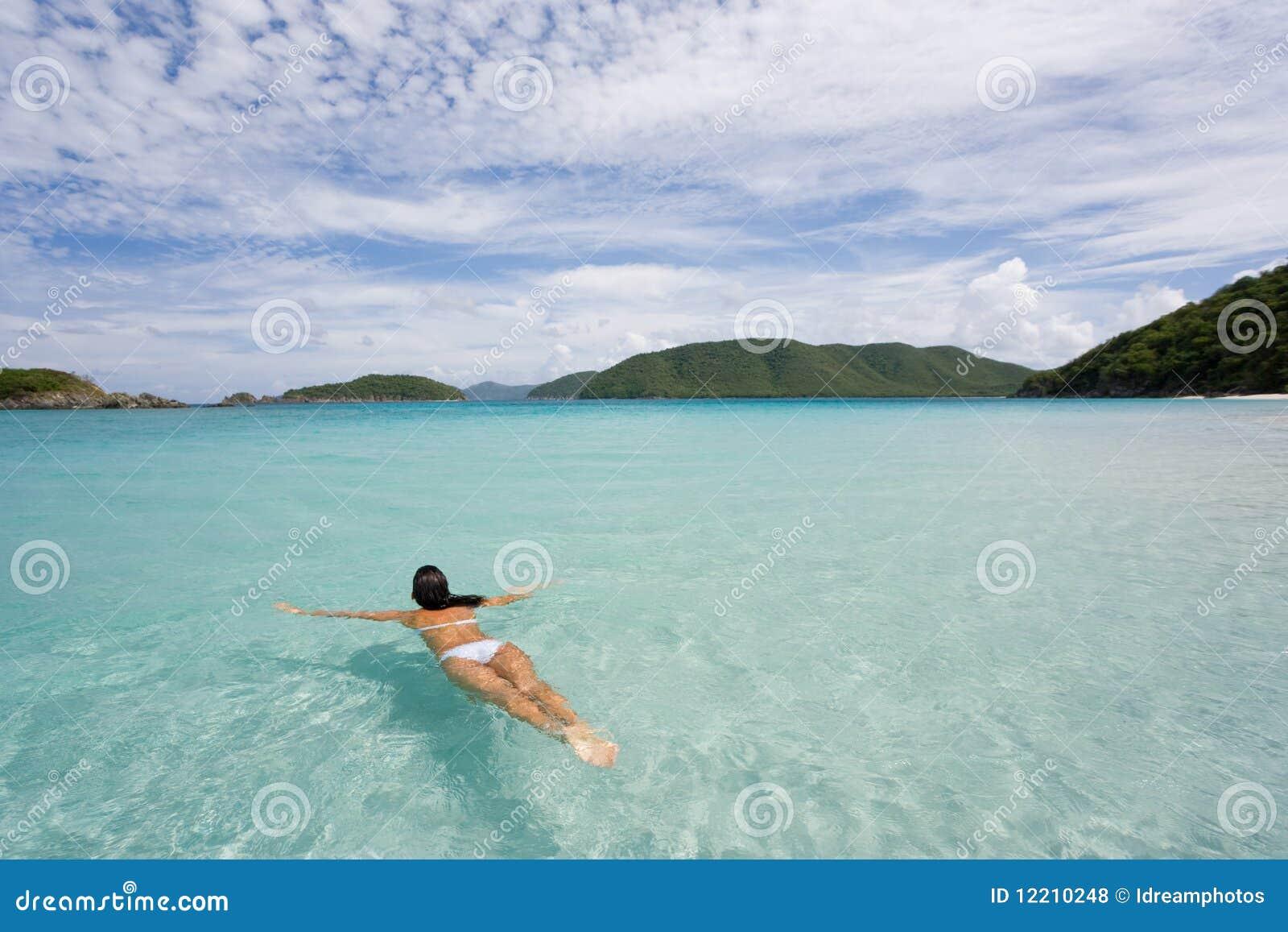 Natação da mulher na água tropical
