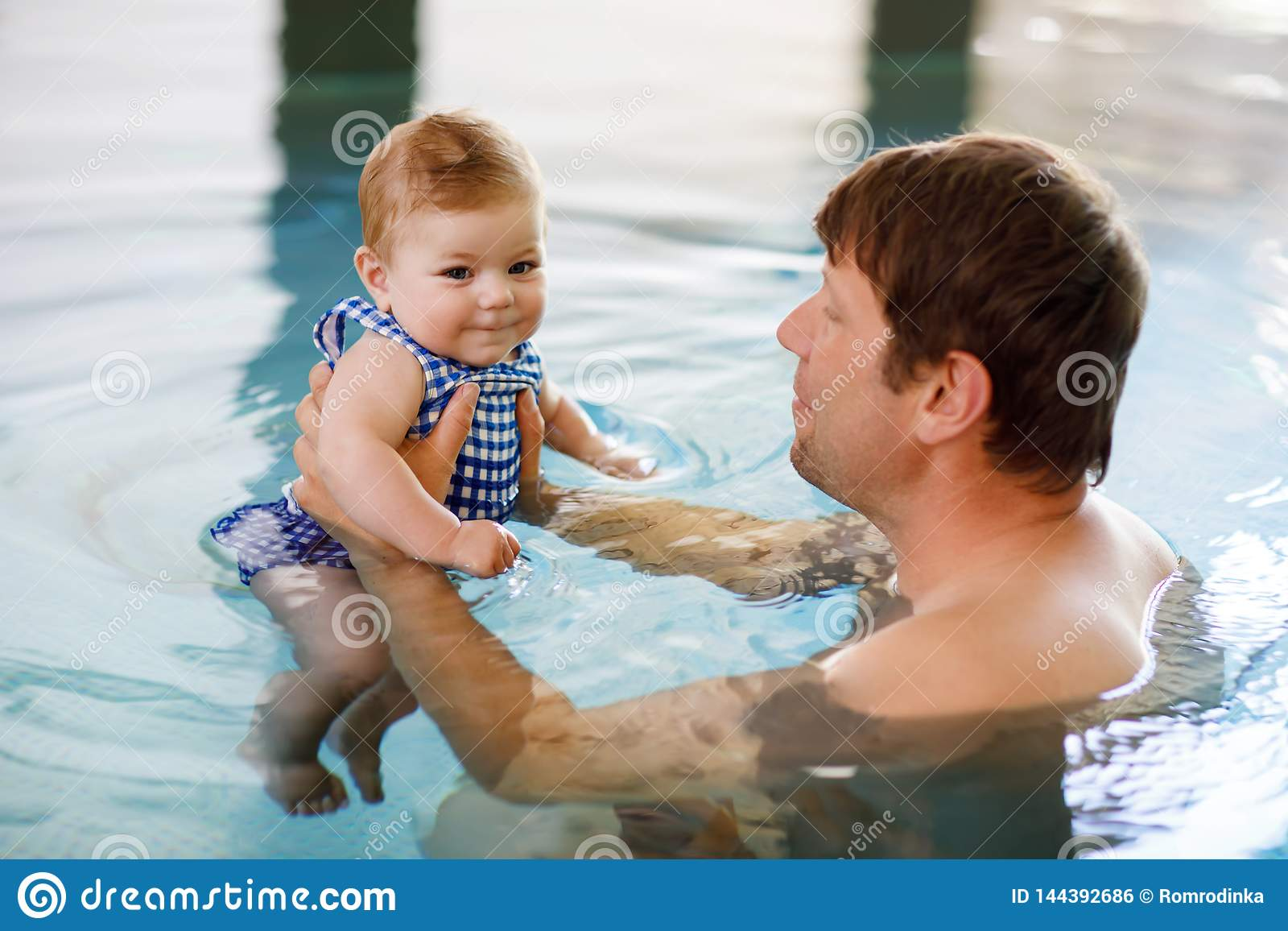 Natação de meia idade feliz do pai com a filha adorável bonito do bebê na associação do giro Paizinho de sorriso e criança pequen