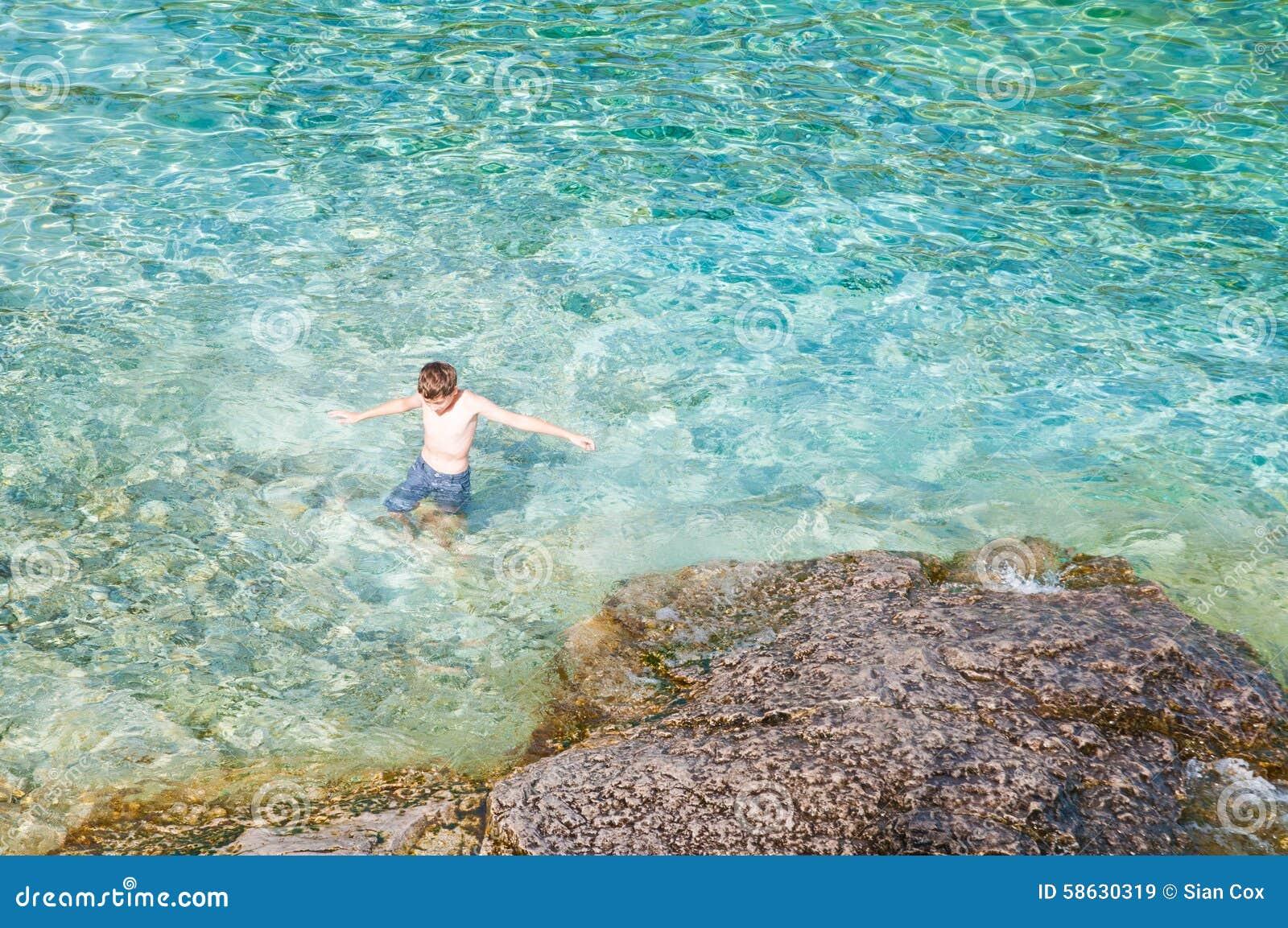 Natação do menino na água claro de turquesa