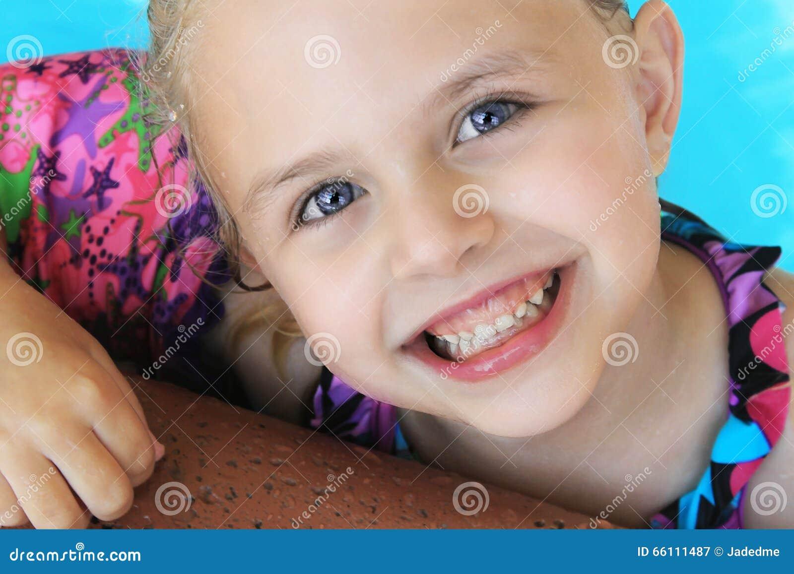 Natação loura pequena da menina na associação no verão
