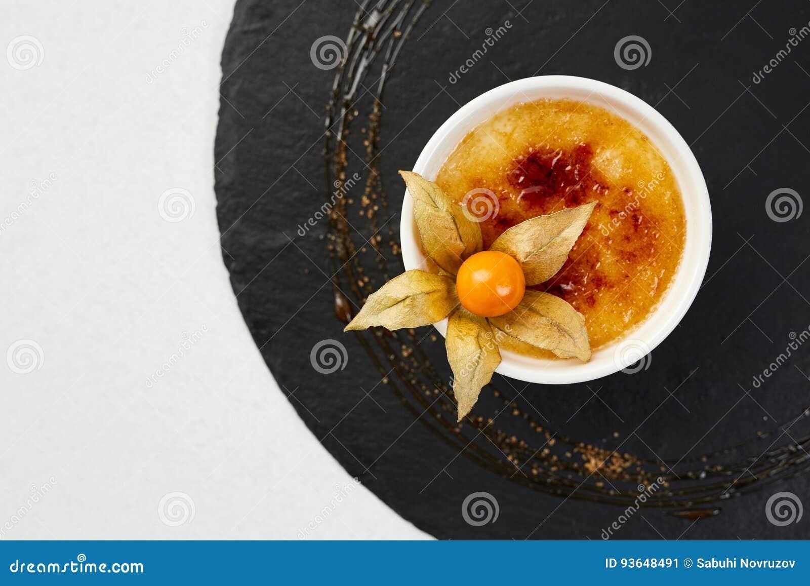 Nata quemada con el Physalis y el azúcar marrón Postre quemado de la nata en el esquisto negro
