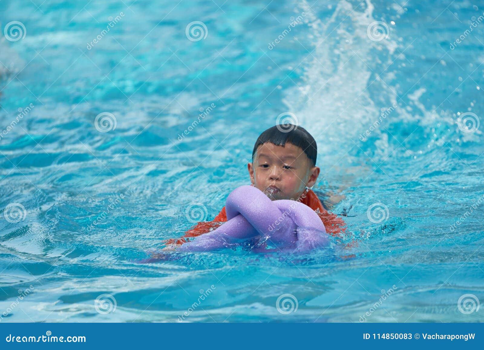 Natación de la práctica del muchacho con el flotador de la espuma de los tallarines