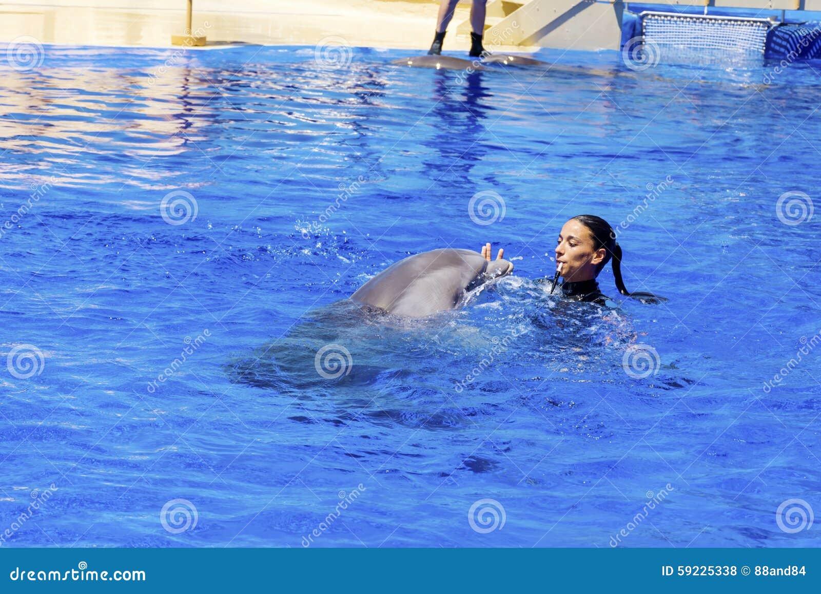 Natación del instructor de la mujer con los delfínes