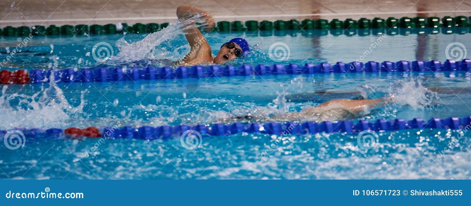 Natación del muchacho en la piscina del deporte