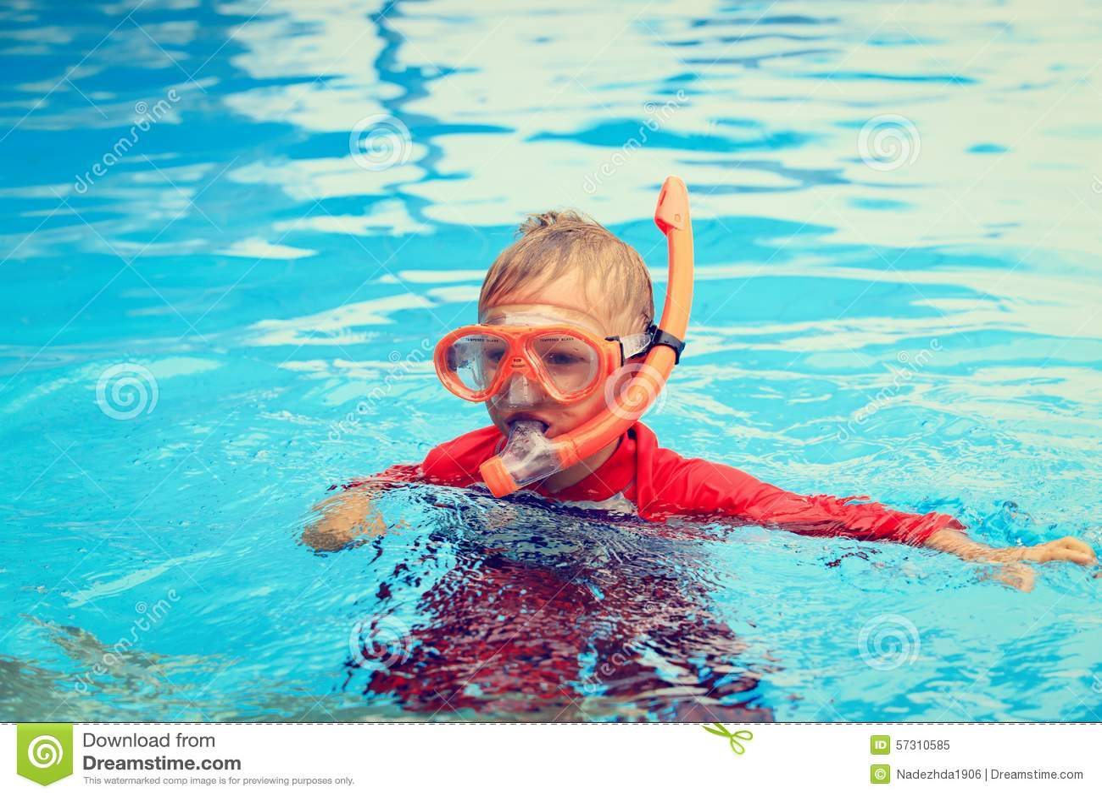 Natación del niño pequeño con la máscara en la piscina