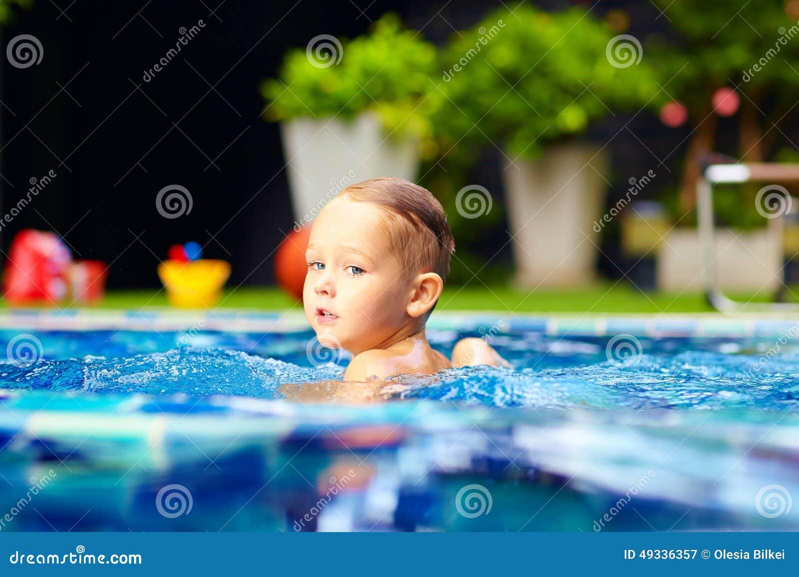 Natación linda del niño pequeño en piscina