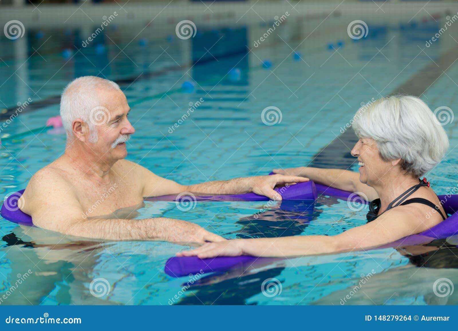Natación mayor feliz de los pares en piscina