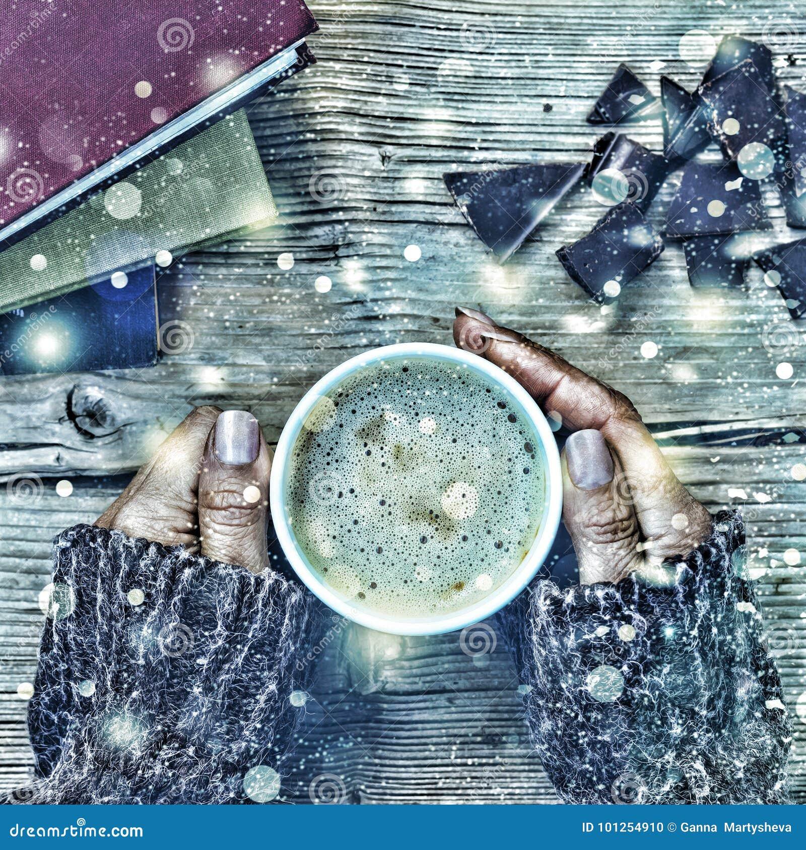 Natal do ano novo Uma xícara de café ou um copo do chá em sua mão, e em mulheres esmagaram o chocolate escuro, pilha de livros Sn