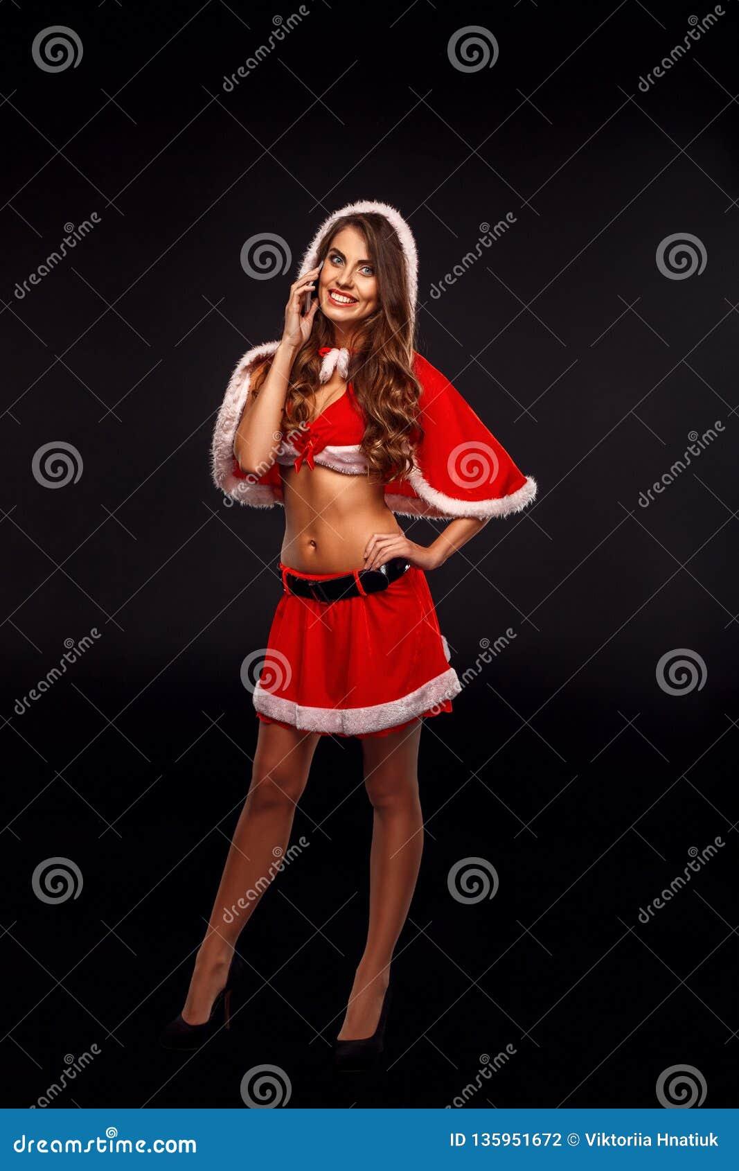 Natal e ano novo Mulher no traje de Santa com posição da capa isolado no levantamento preto à chamada de resposta da câmera compl