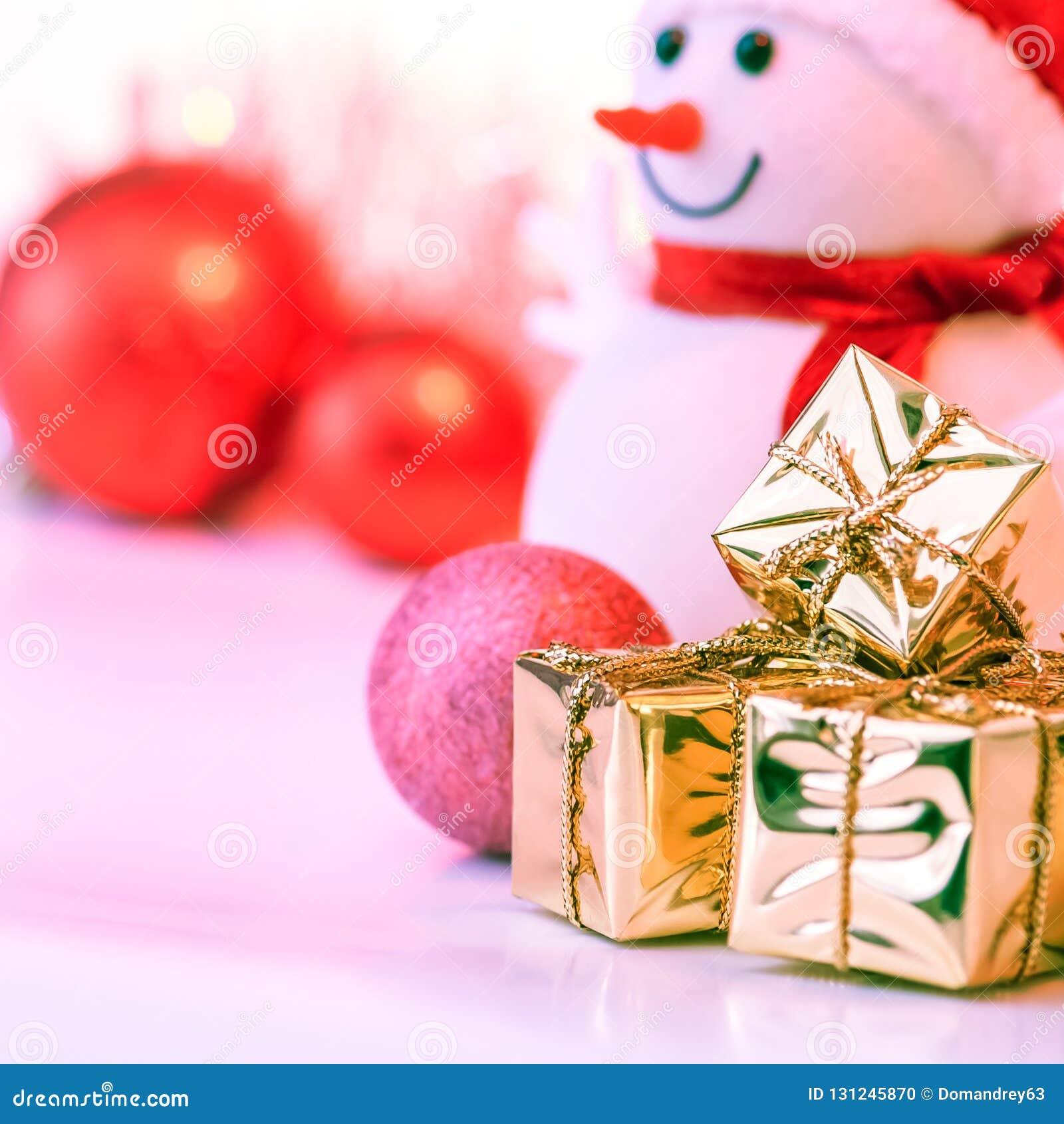 Natal feliz, ano novo, boneco de neve, presentes em umas caixas do ouro e bolas vermelhas em um fundo cor-de-rosa
