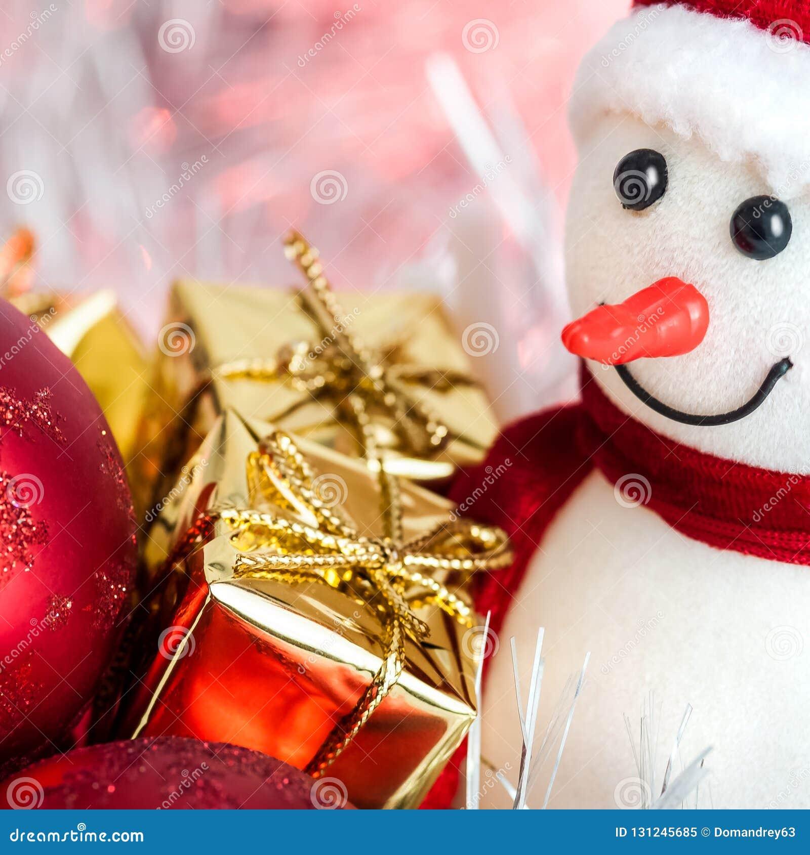 Natal feliz, ano novo, boneco de neve, presentes em umas caixas do ouro e bolas vermelhas em um fundo cor-de-rosa do bokeh