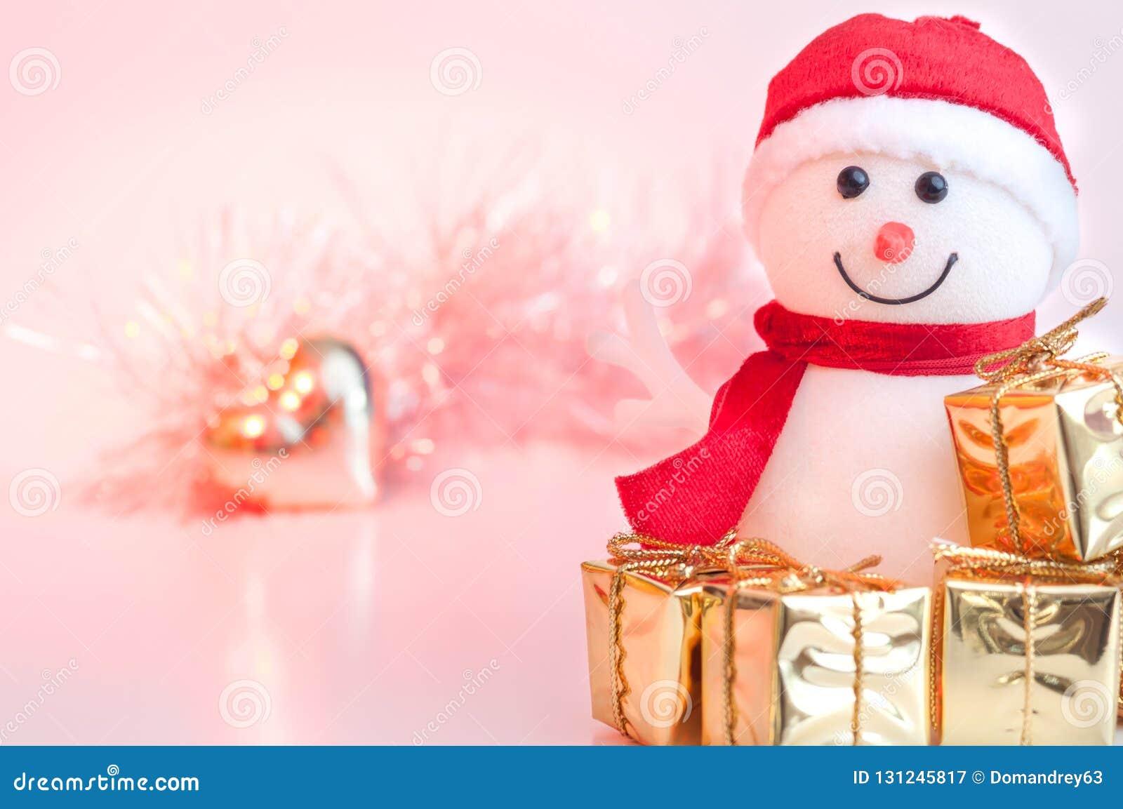 Natal feliz, ano novo, presentes do boneco de neve em umas caixas douradas e um coração dourado em um fundo do rosa e do bokeh am