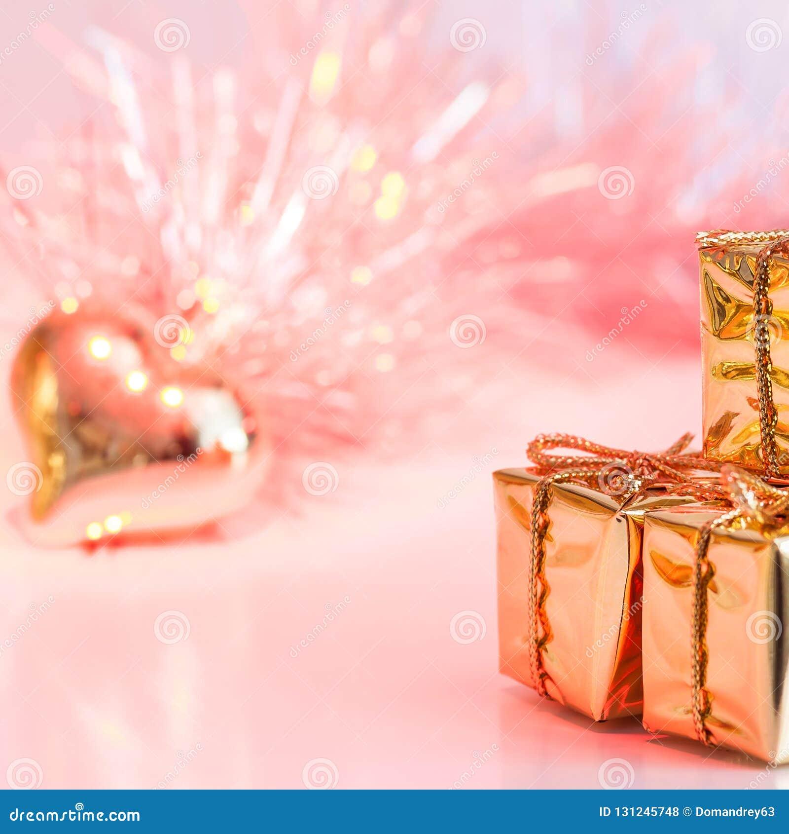 Natal feliz, ano novo, presentes em umas caixas do ouro e um coração dourado em um fundo do rosa e do bokeh amarelo