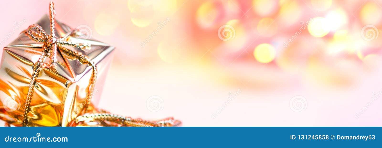 Natal feliz, ano novo, presentes em umas caixas do ouro em um fundo do rosa e bokeh amarelo