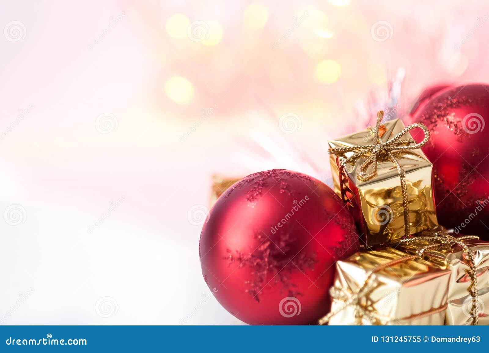 Natal feliz, ano novo, presentes nas caixas do ouro, bolas vermelhas do Natal no canto direito Fundo Bokeh