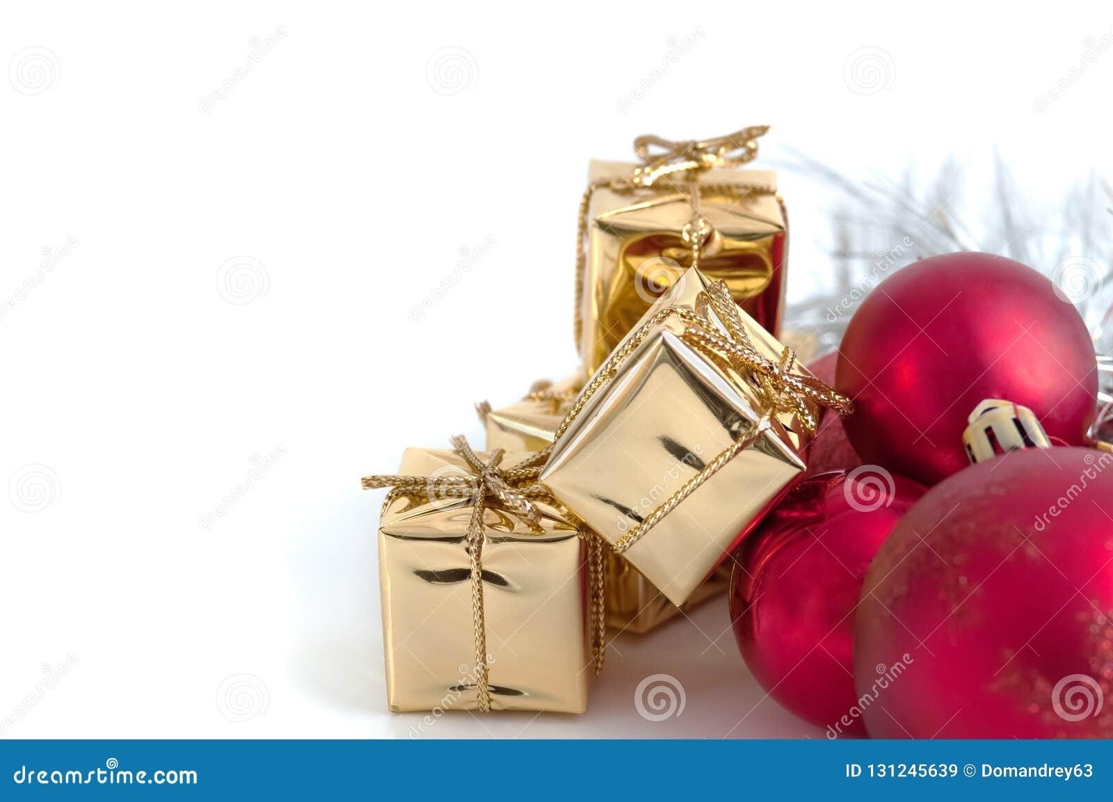 Natal feliz, ano novo, presentes nas caixas do ouro, bolas vermelhas do Natal no canto direito Fundo branco