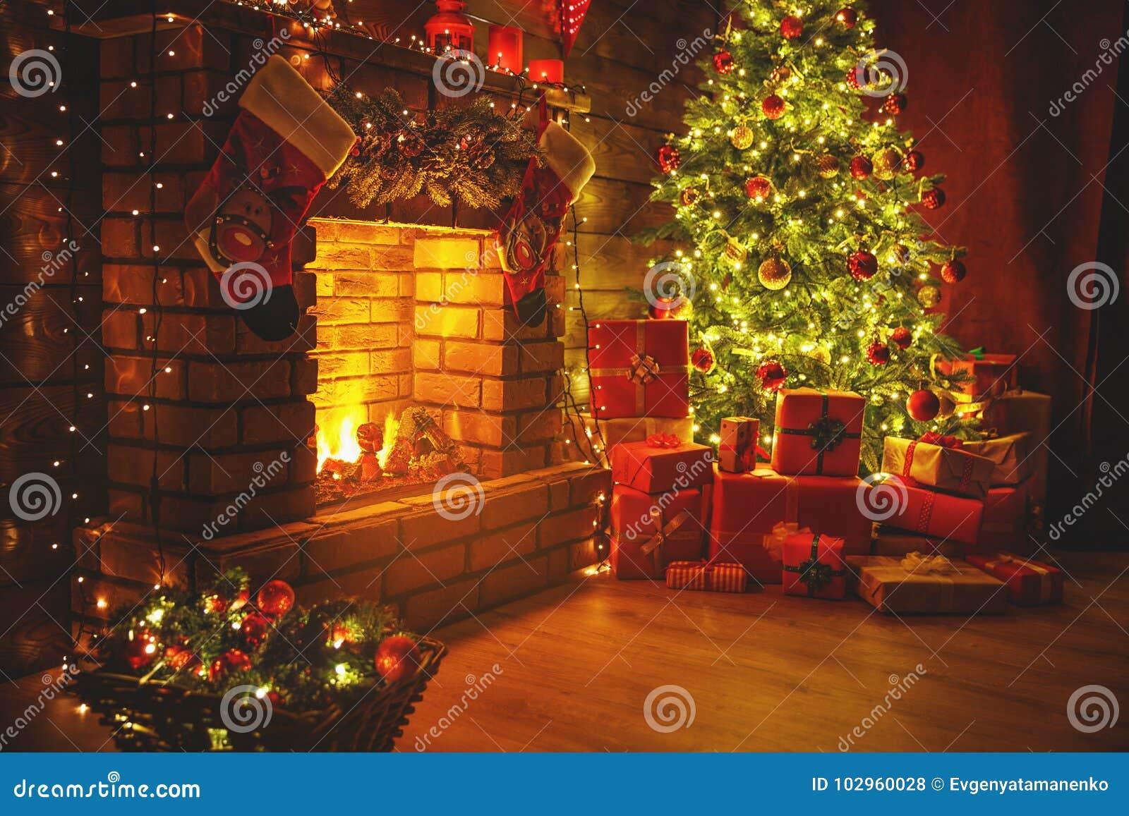 Natal interior árvore de incandescência mágica, presentes da chaminé na obscuridade