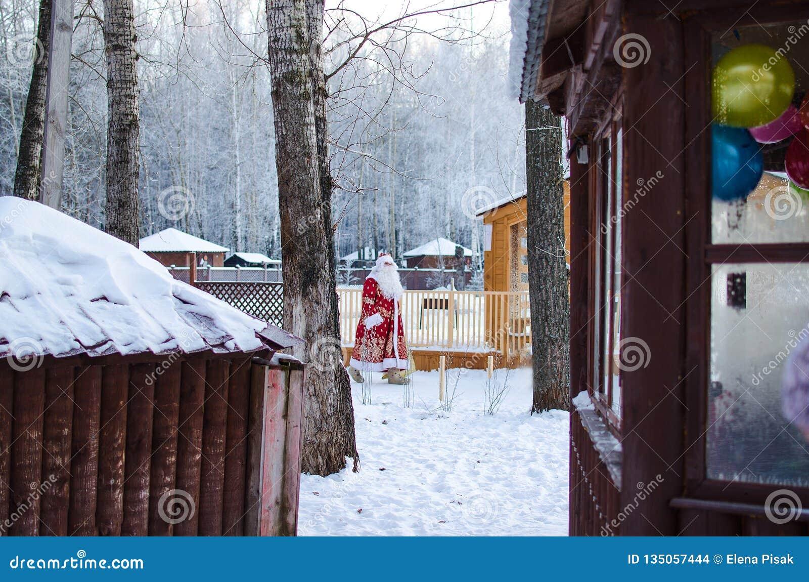 Natale, freddo, dicembre Santa Claus che va con una borsa dei regali nell inverno sul campo innevato