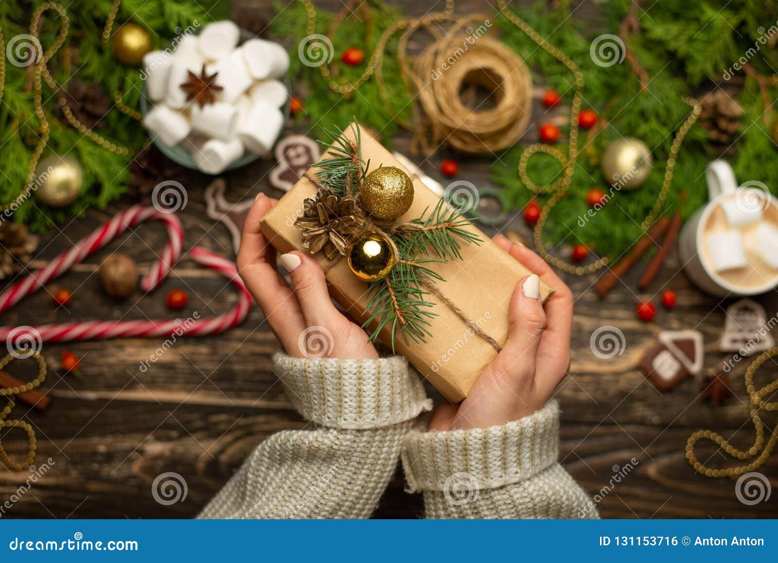 Natale, il fondo del nuovo anno, piano-disposizione la ragazza in un maglione di lana avvolge i regali su un fondo di legno, con