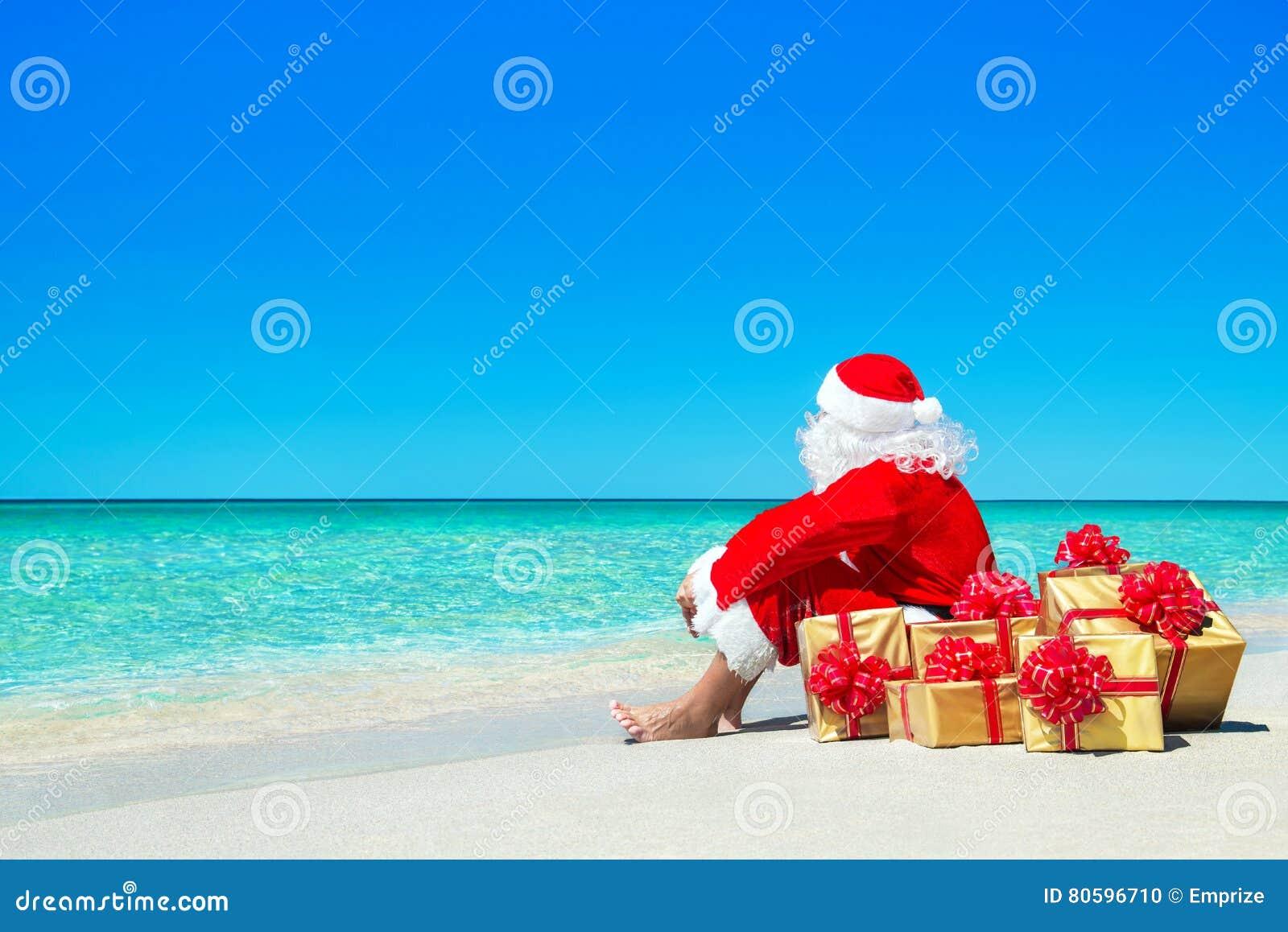Natale Santa Claus con i contenitori di regalo che si rilassano alla spiaggia dell oceano