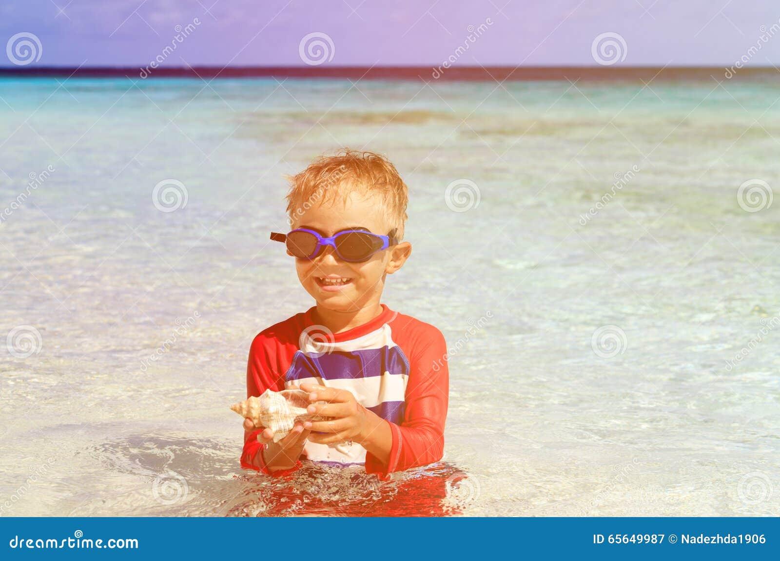 Natation de petit garçon tenant la coquille sur la plage