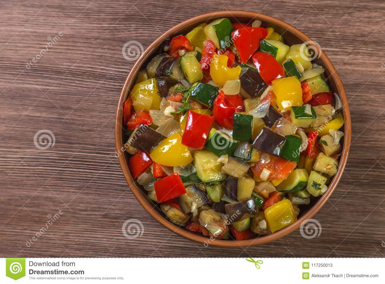 Provencal dish Ratatouille in a pot made of ceramics on the table made of oak planks. Brown. Proper nutrition and diet concept. Br